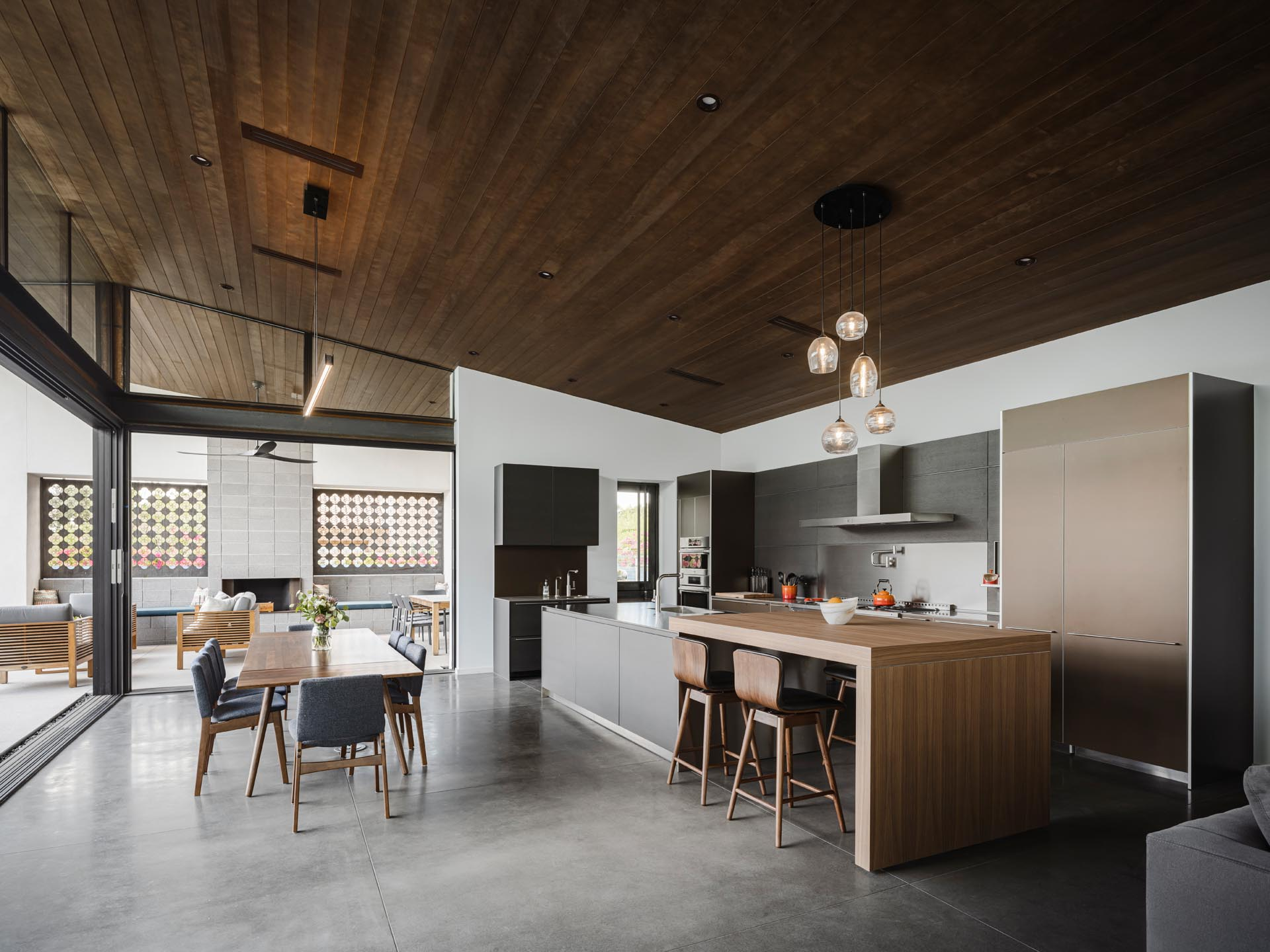 The open plan dining room and kitchen of this modern home includes concrete flooring, a wood dining table, and a large kitchen with an expansive island with a raised section that acts as a bar.