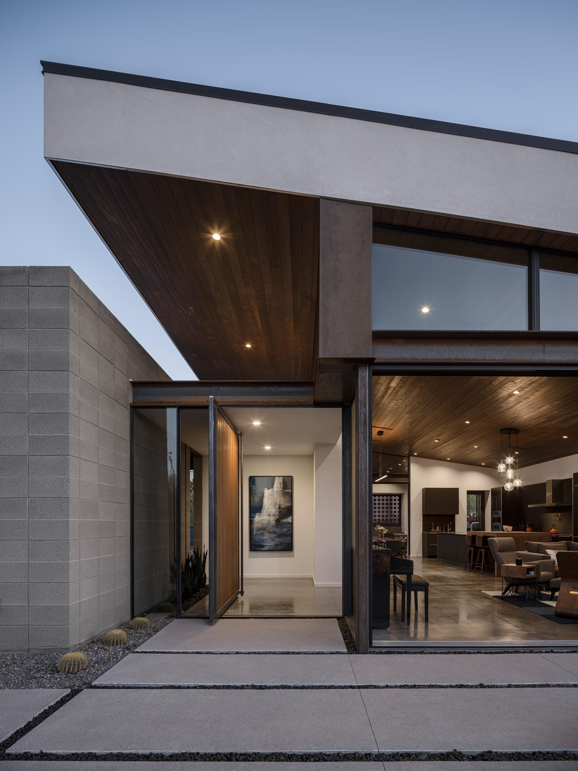 An oversized wood front door with a metal frame pivots to create an eye-catching entryway that opens to a foyer. A small garden is featured on both the exterior and interior of the home.