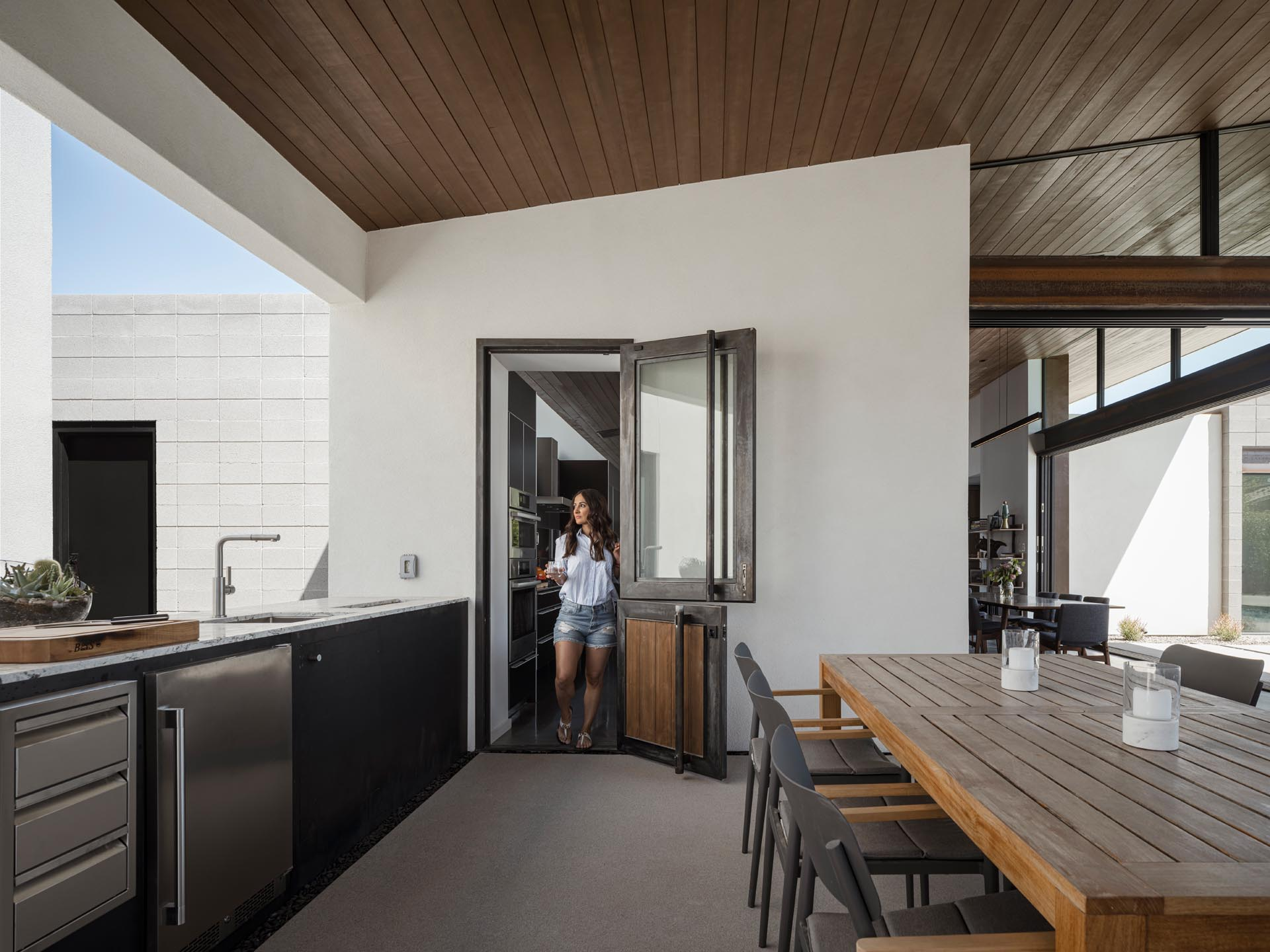 This modern covered patio includes a fireplace that is also used for cooking, built-in benches that flank the fireplace, an outdoor kitchen and dining area, a lounge area, and a customized screen with their family emblem.