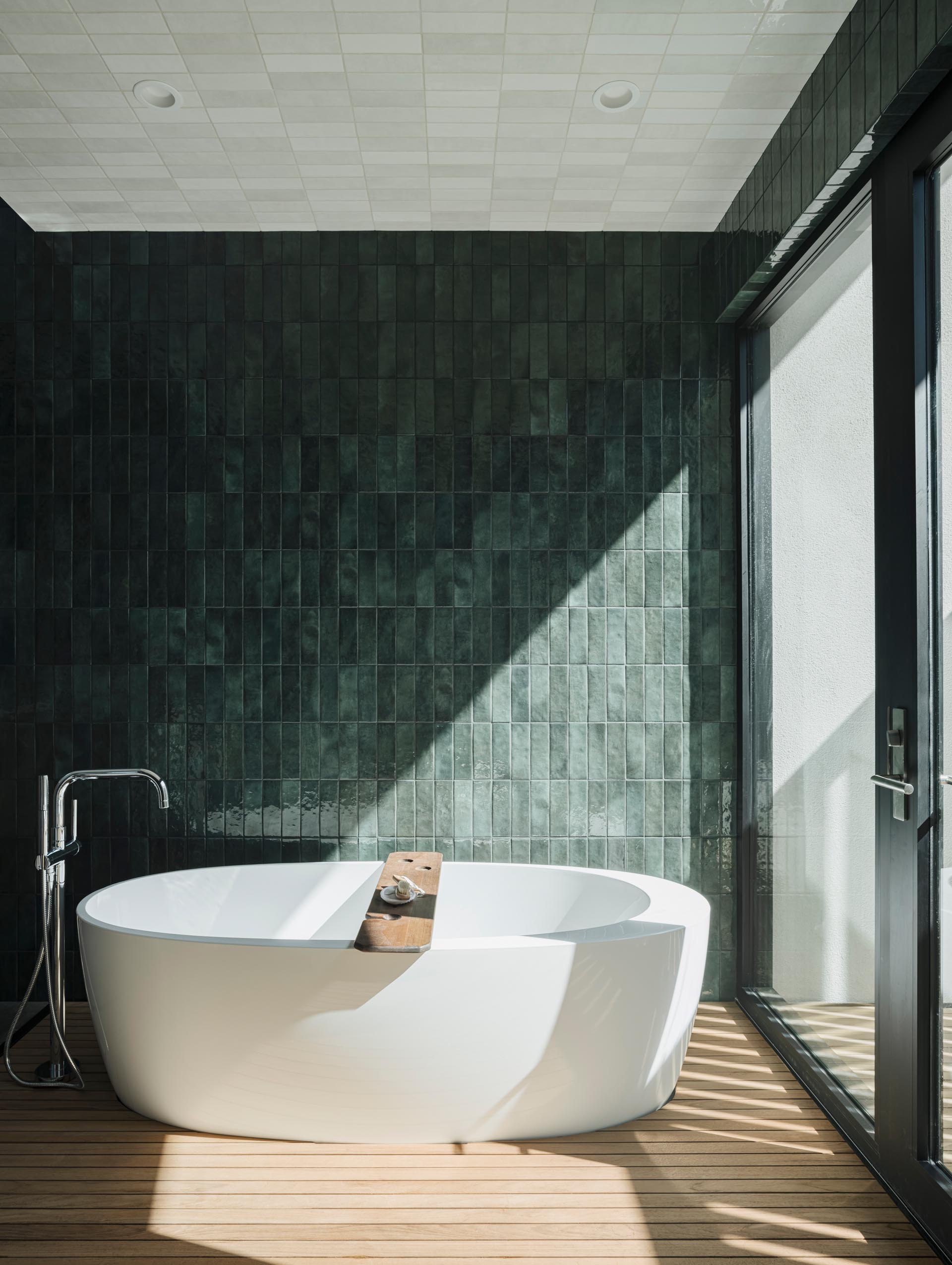 A modern bathroom with a naturally lit shower and bathing area that opens out to an outdoor shower, screened from the nearby neighbor with a custom steel slatted wall. Glazed green wall tiles have been used to create a unique look for the bathroom.