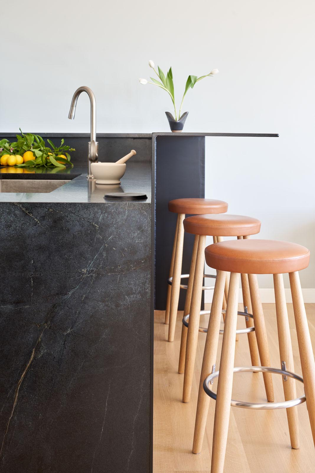 This modern kitchen has dark countertops that connect with a raised steel breakfast bar.