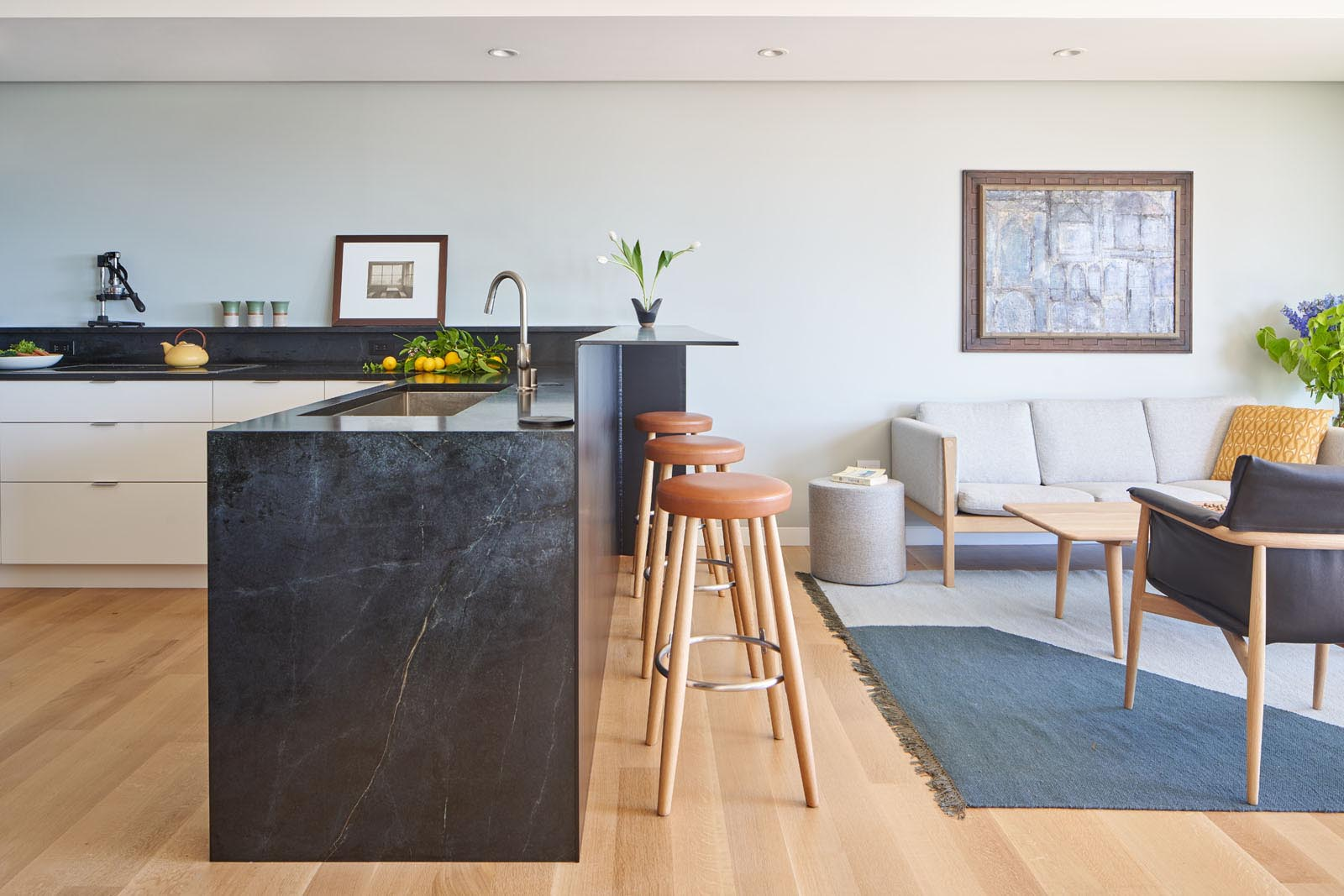 This modern kitchen has been designed with a wall of white cabinetry that wraps around to become lower cabinets, while the dark countertop connects with a raised steel breakfast bar.