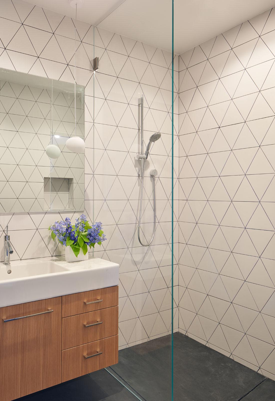 In this modern bathroom, triangular tiles cover the walls with the dark grout used to highlight the design.
