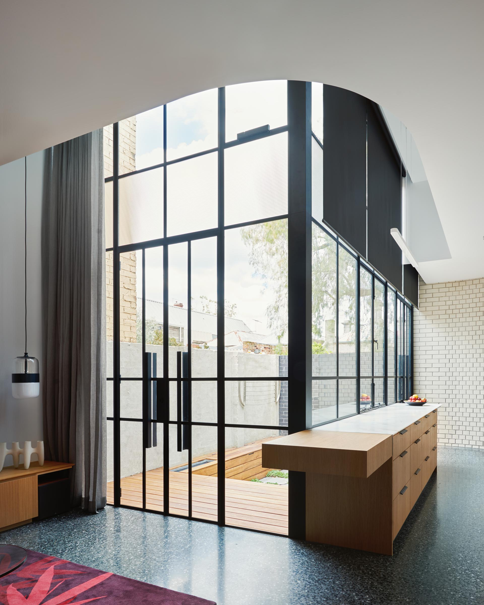 Black framed glass doors which blend into the glass walls, help to create an abundance of natural light that filters through to the interior.