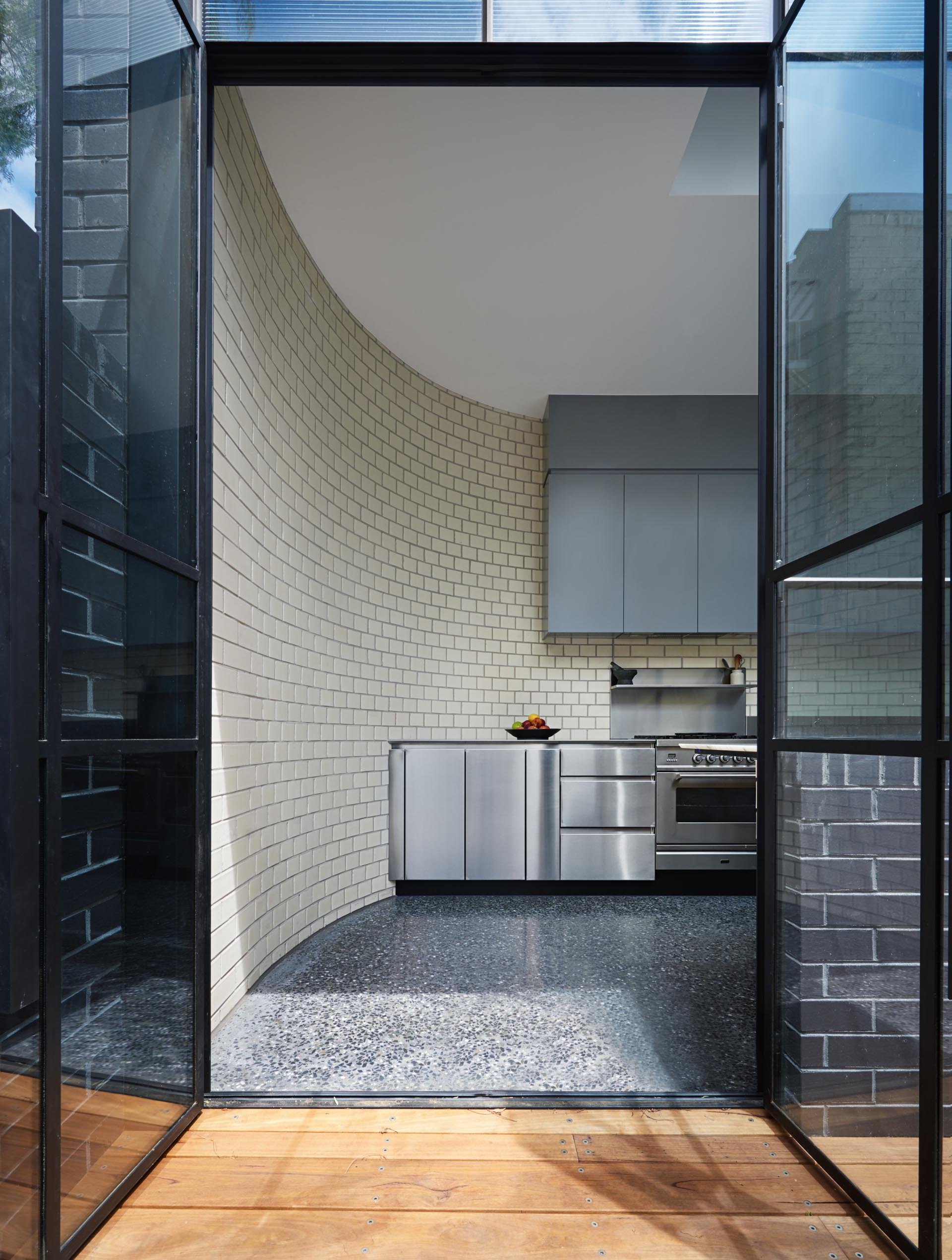 This modern kitchen is designed with a curved white brick wall, stainless steel lower cabinets, and minimalist upper cabinets with a matte finish. Opposite this wall of cabinetry, is a long timber countertop with built-in marble section for kneading dough.