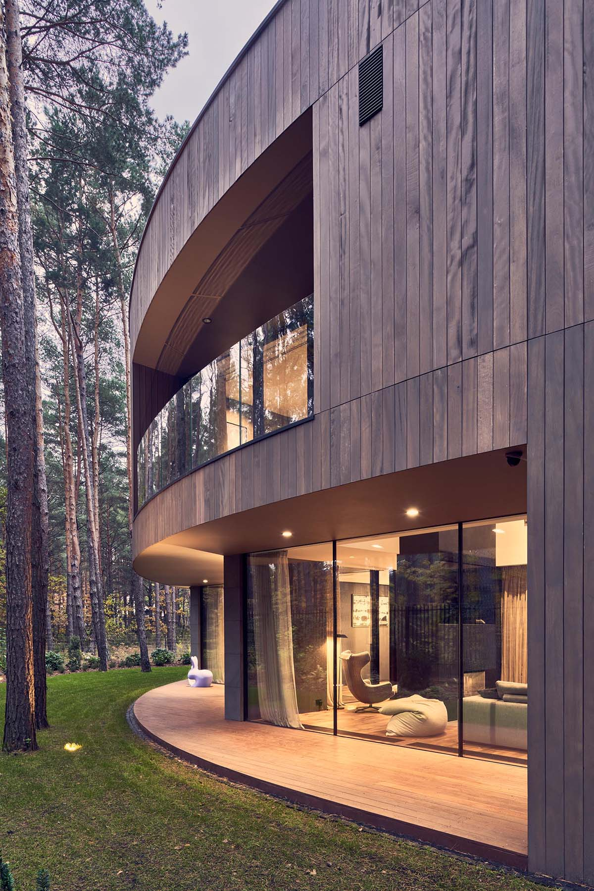A modern circular home with a wood exterior and large windows that provide a glimpse of the interior.
