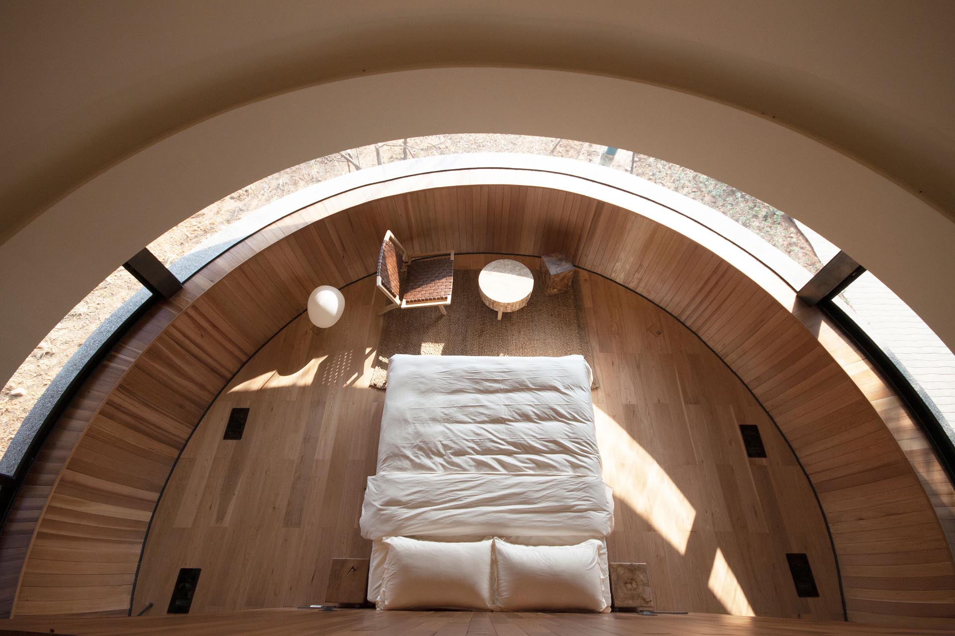 Inside this modern cabin, there's a bedroom that's designed to take advantage of the panoramic window that's curved to the shape of the wall.