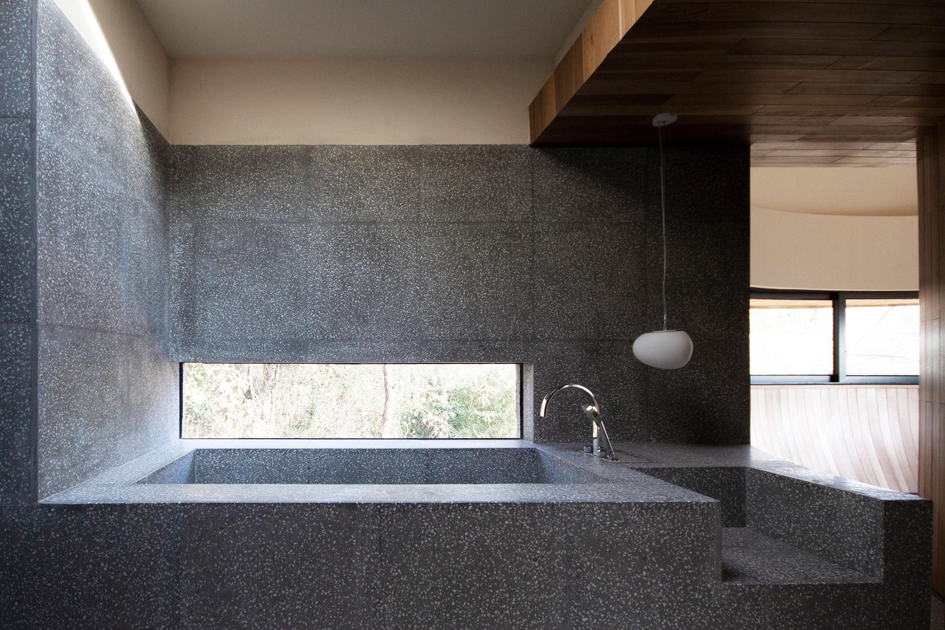 In this modern bathroom, there's a built-in bathtub with a horizontal window, which was designed to ensure privacy from the walking paths outside, while still allowing views of nature.