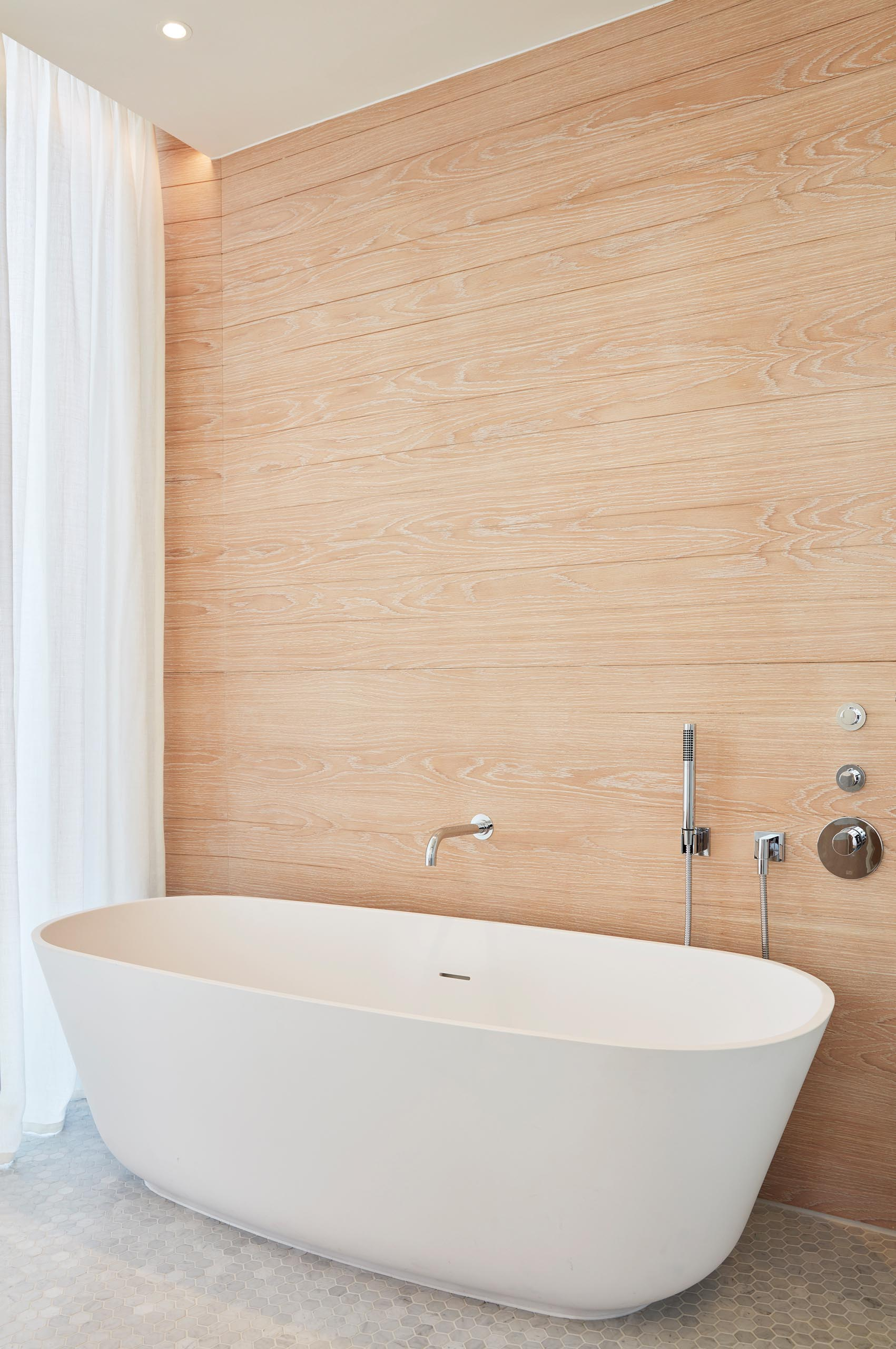 A wood accent wall acts as a backdrop for a freestanding white bathtub.
