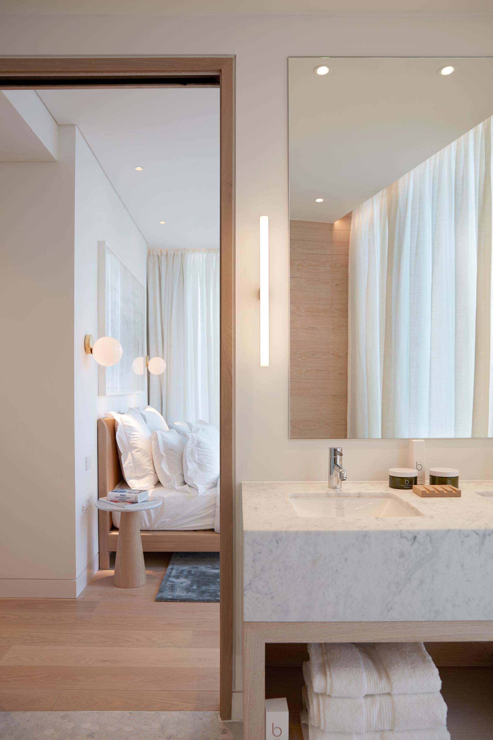 In an modern bathroom, light wood has been used for the open vanity shelving, as well as the accent wall that's installed behind the freestanding white bathtub, while the vanity countertop complements the walk-in shower.