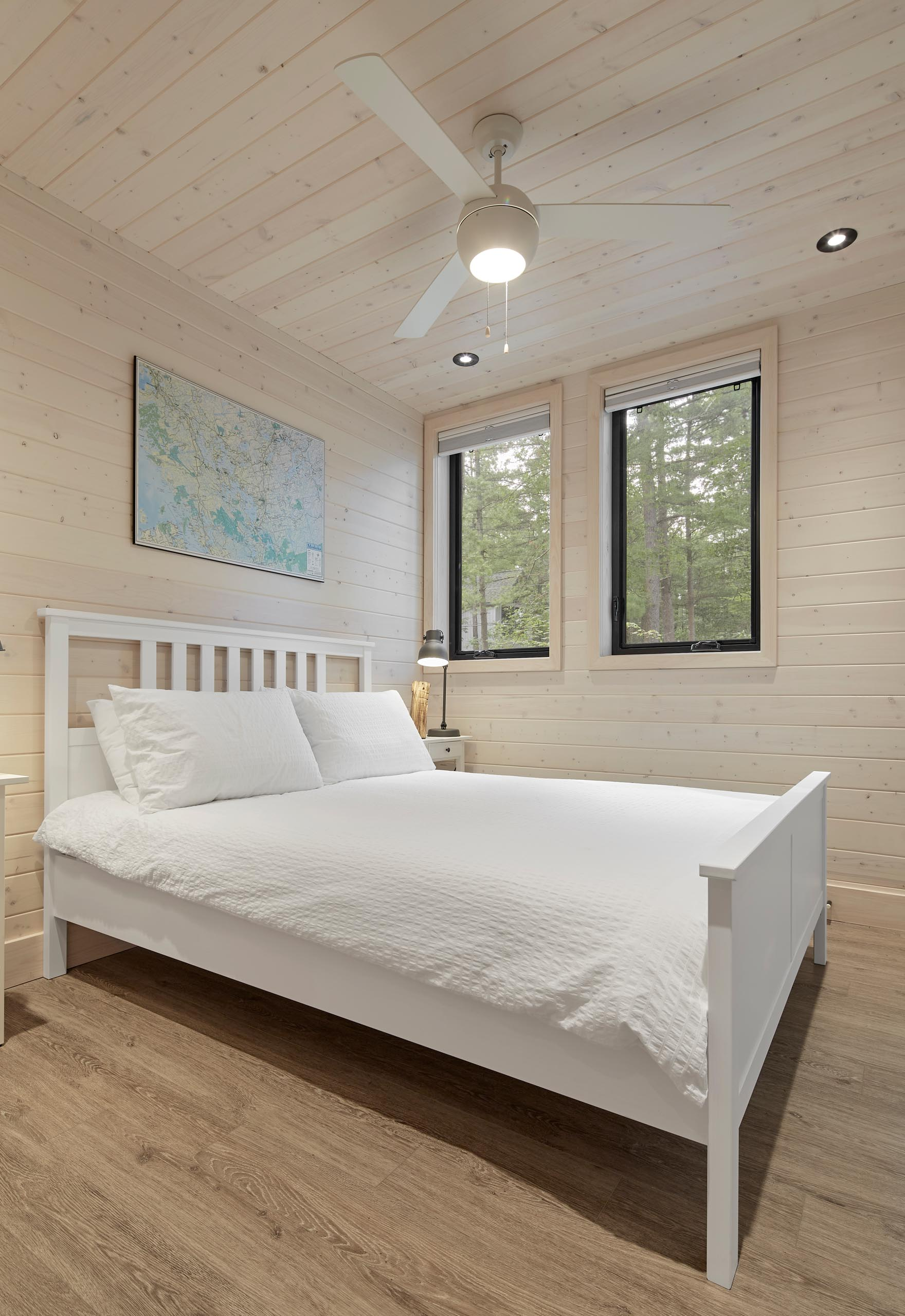 A modern cottage bedroom with light wood walls and ceiling.