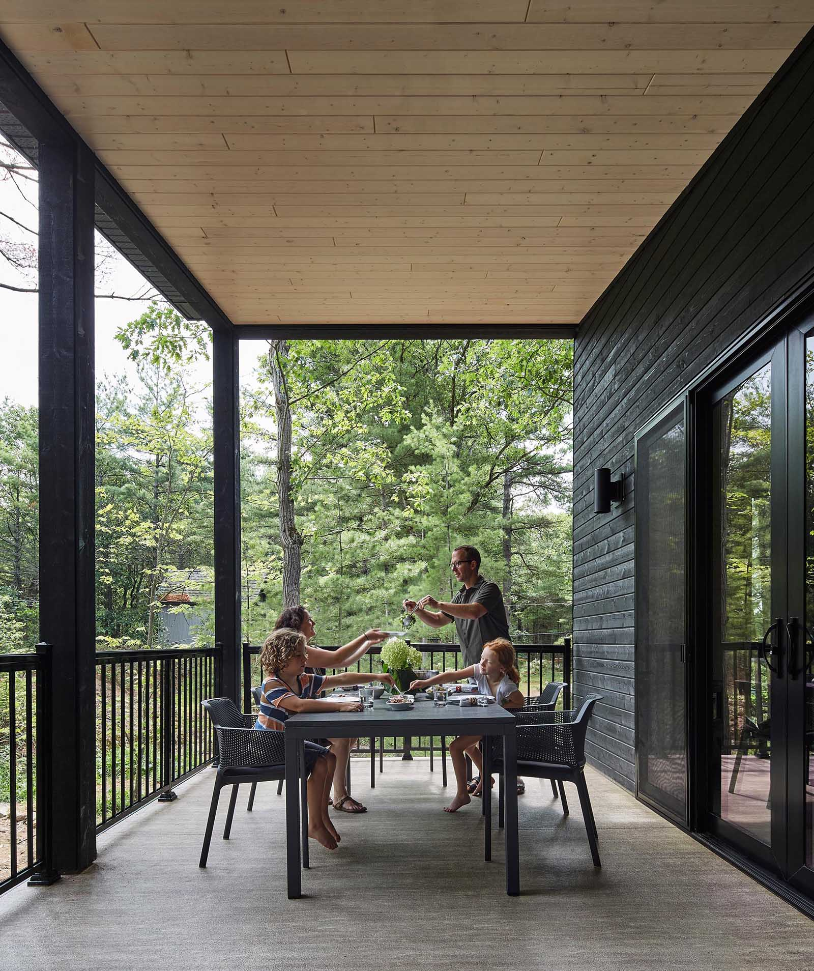 A modern cottage with a covered outdoor dining area.