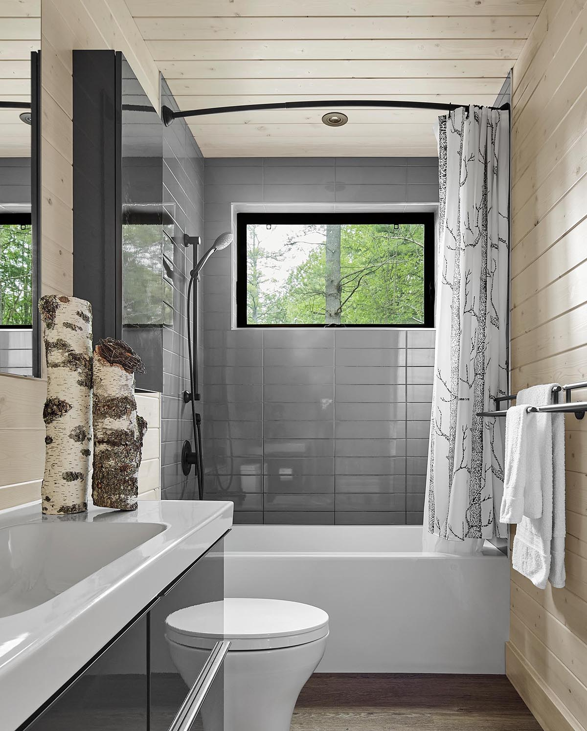 A modern gray and wood bathroom with black and white accents.