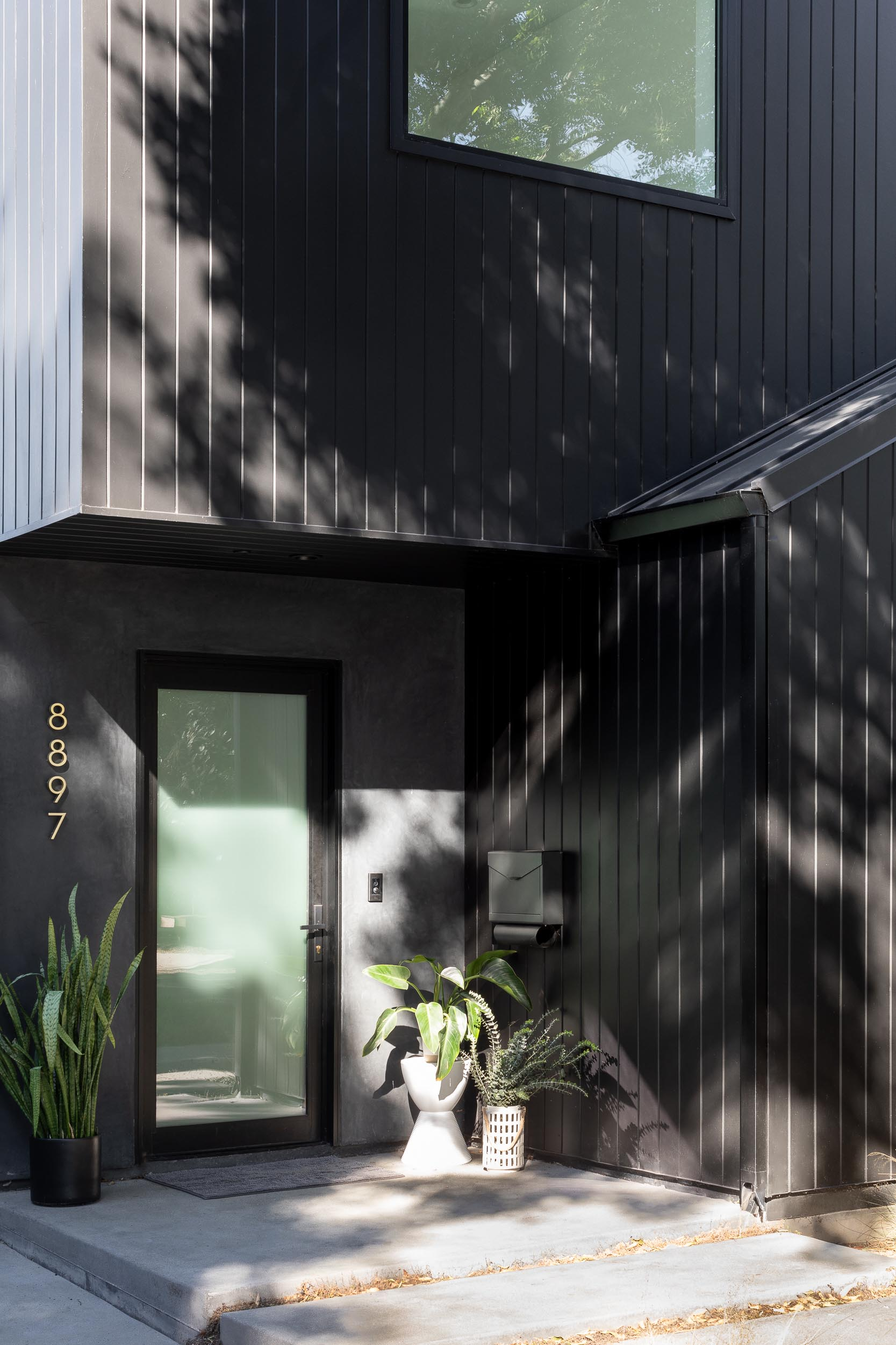 The dark and moody black exterior of this modern home was inspired by Japanese traditions like Shou Sugi Ban, while the design of the home evokes the familiar footprint of a traditional barn.