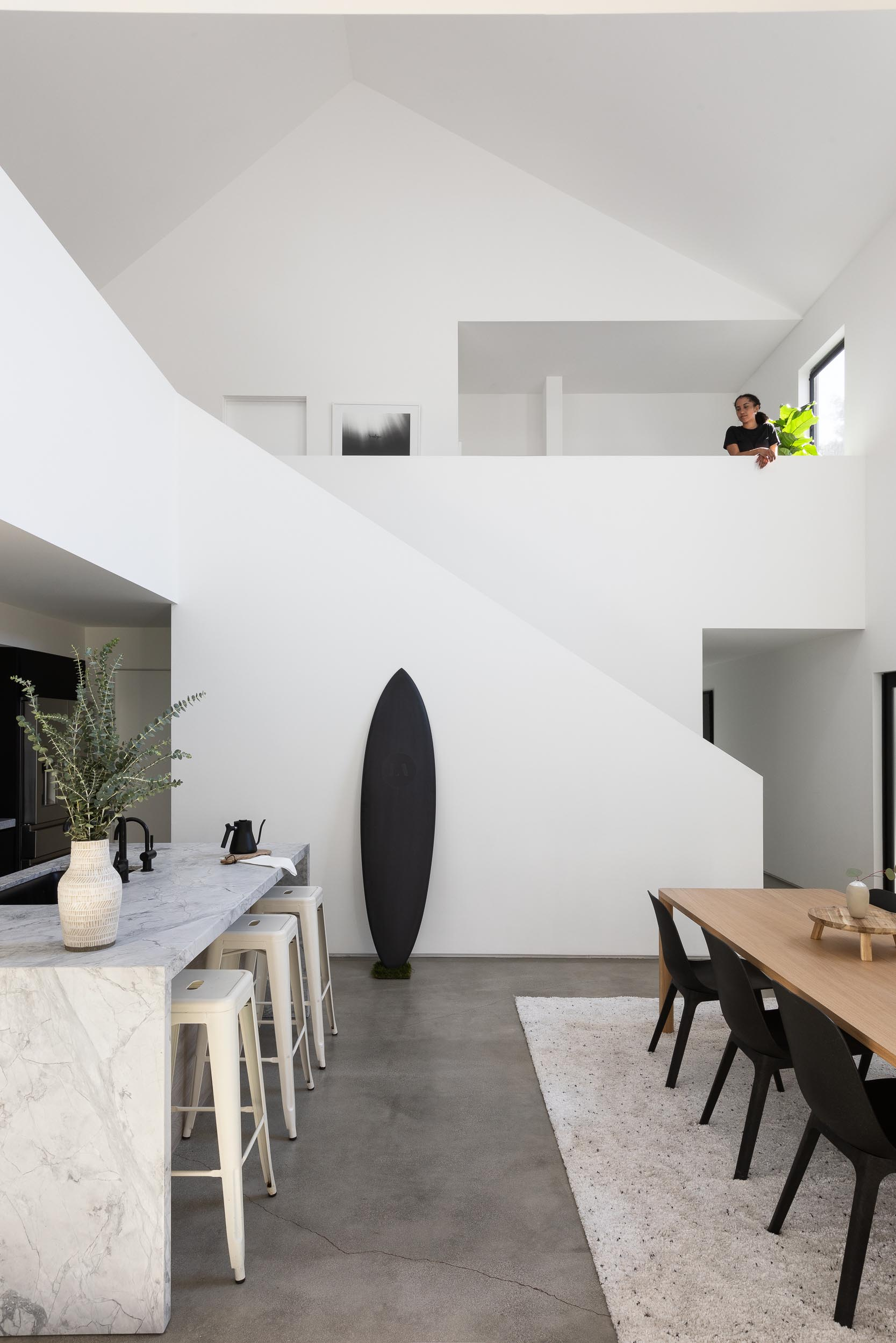 This modern home interior has the dining room next to the kitchen island, which was designed with with room for seating, while the kitchen has matte black lower cabinets and light wood upper cabinets.