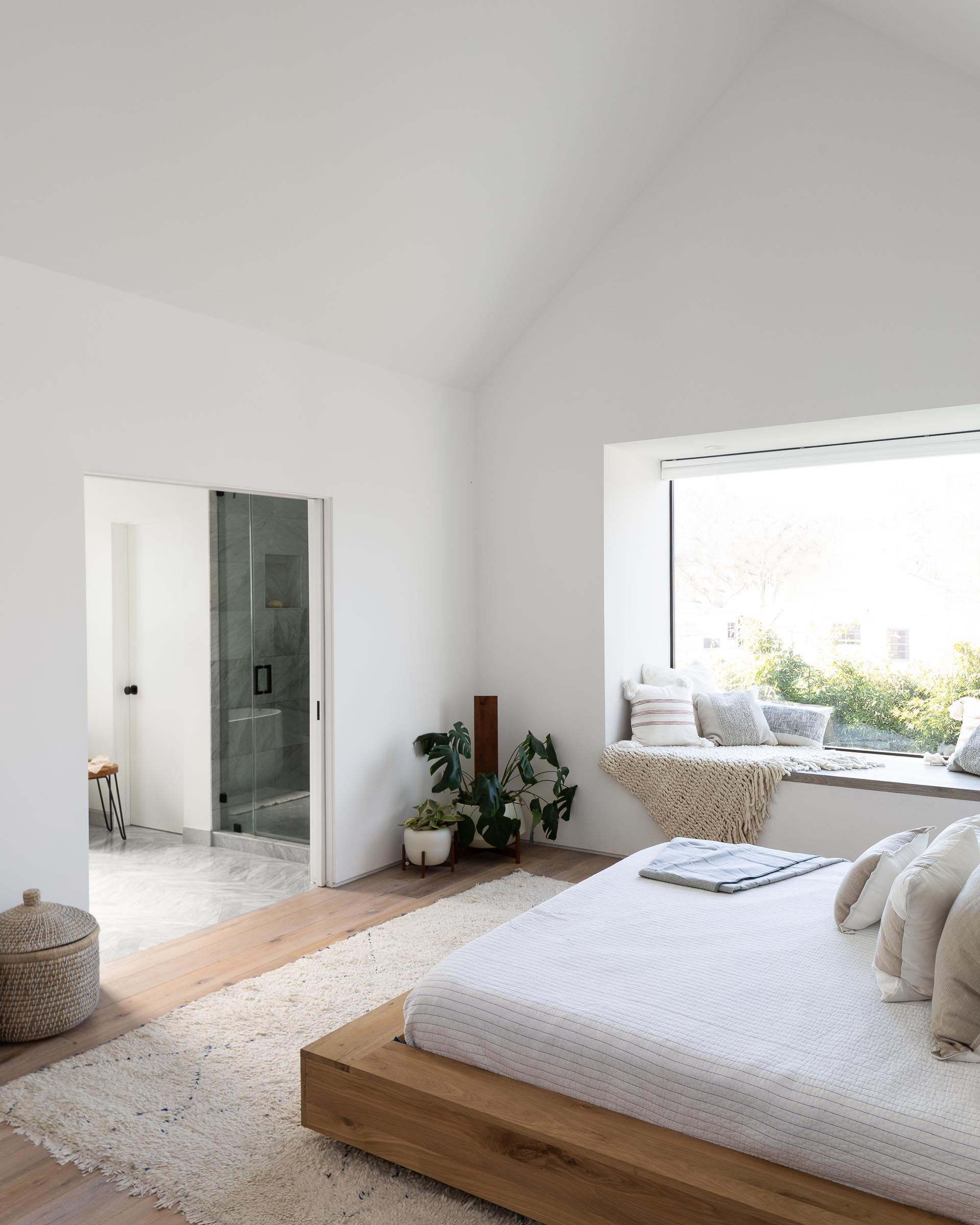 In this modern bedroom, a wood bed frame and side tables add warmth to the space, while a window seat creates a cozy place to read a book and take in the views of the yard.