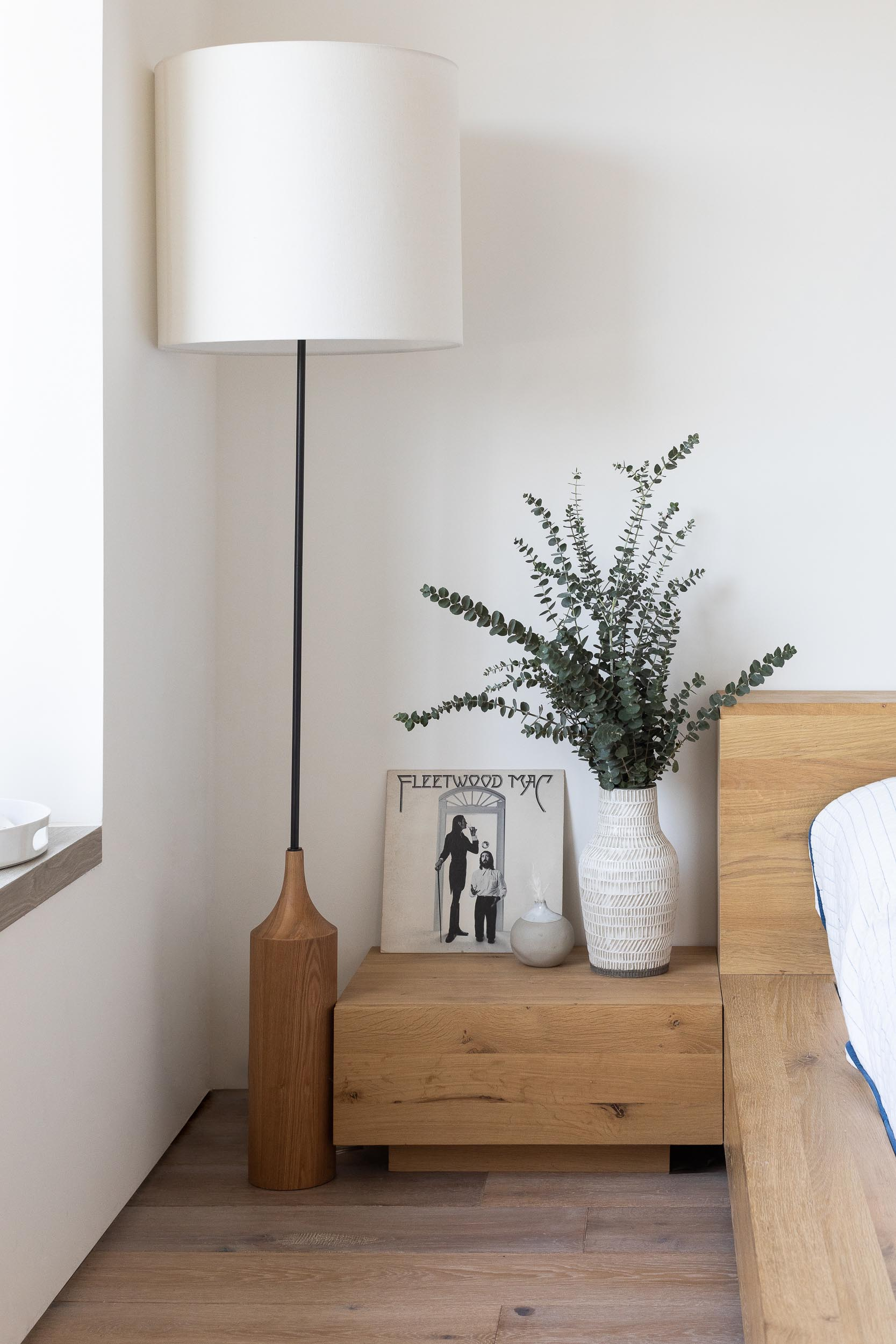 A modern bedroom with a wood bed frame and chunky wood side tables.