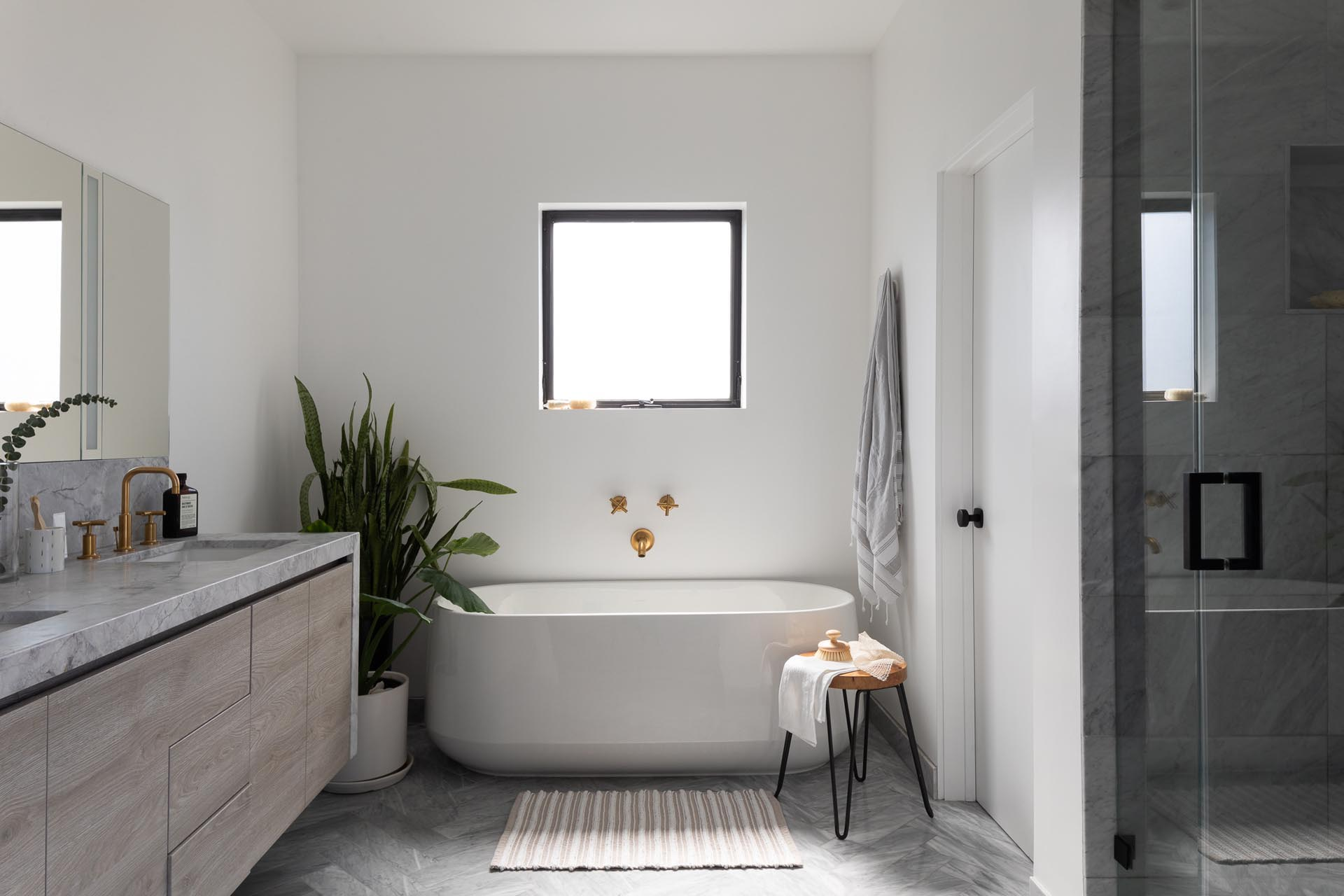 In this modern en-suite bathroom, there's a freestanding white bathtub, a walk-in shower, and a wood vanity with a waterfall countertop.