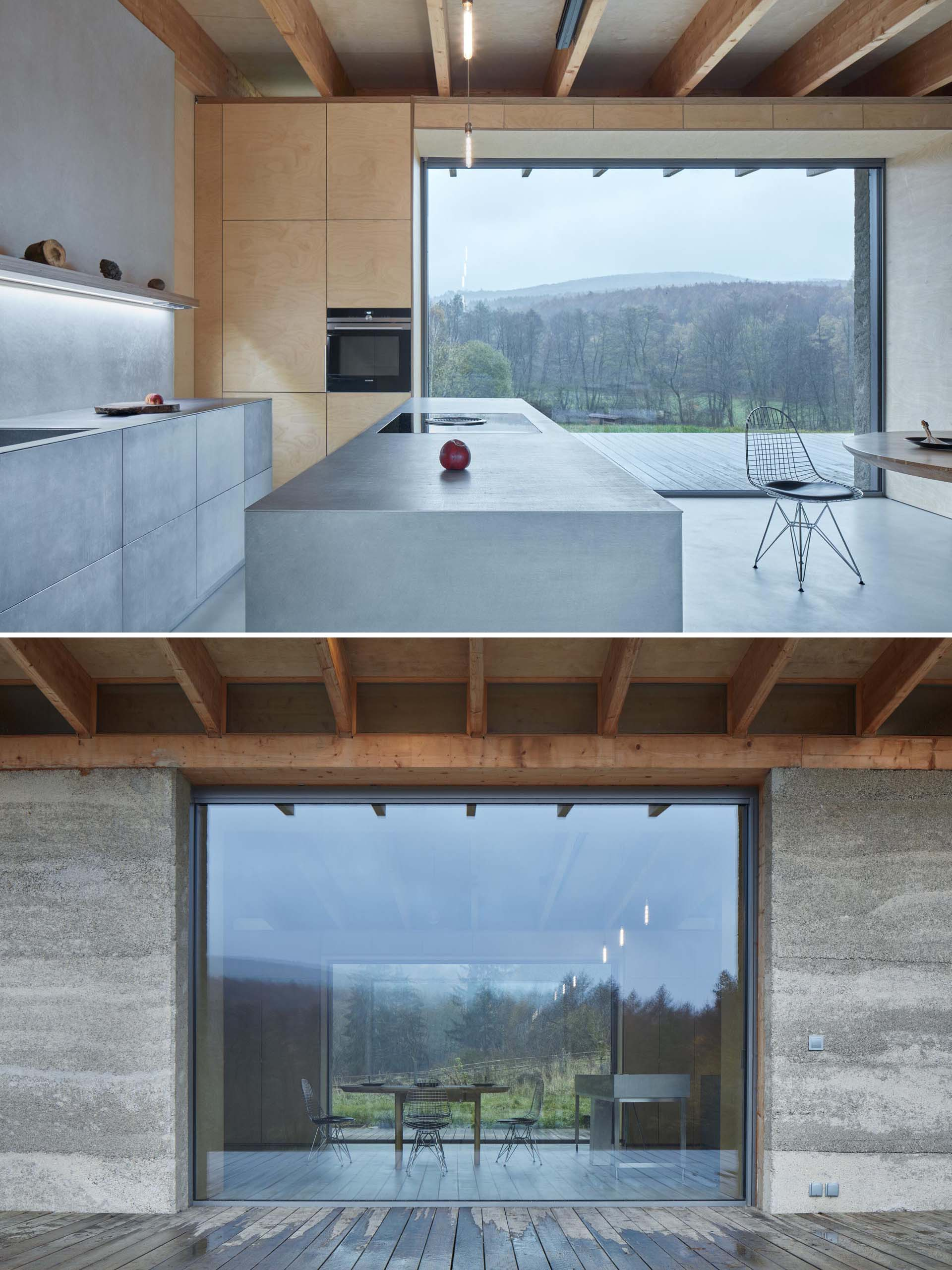 A modern cabin with a stainless steel kitchen and plywood walls.
