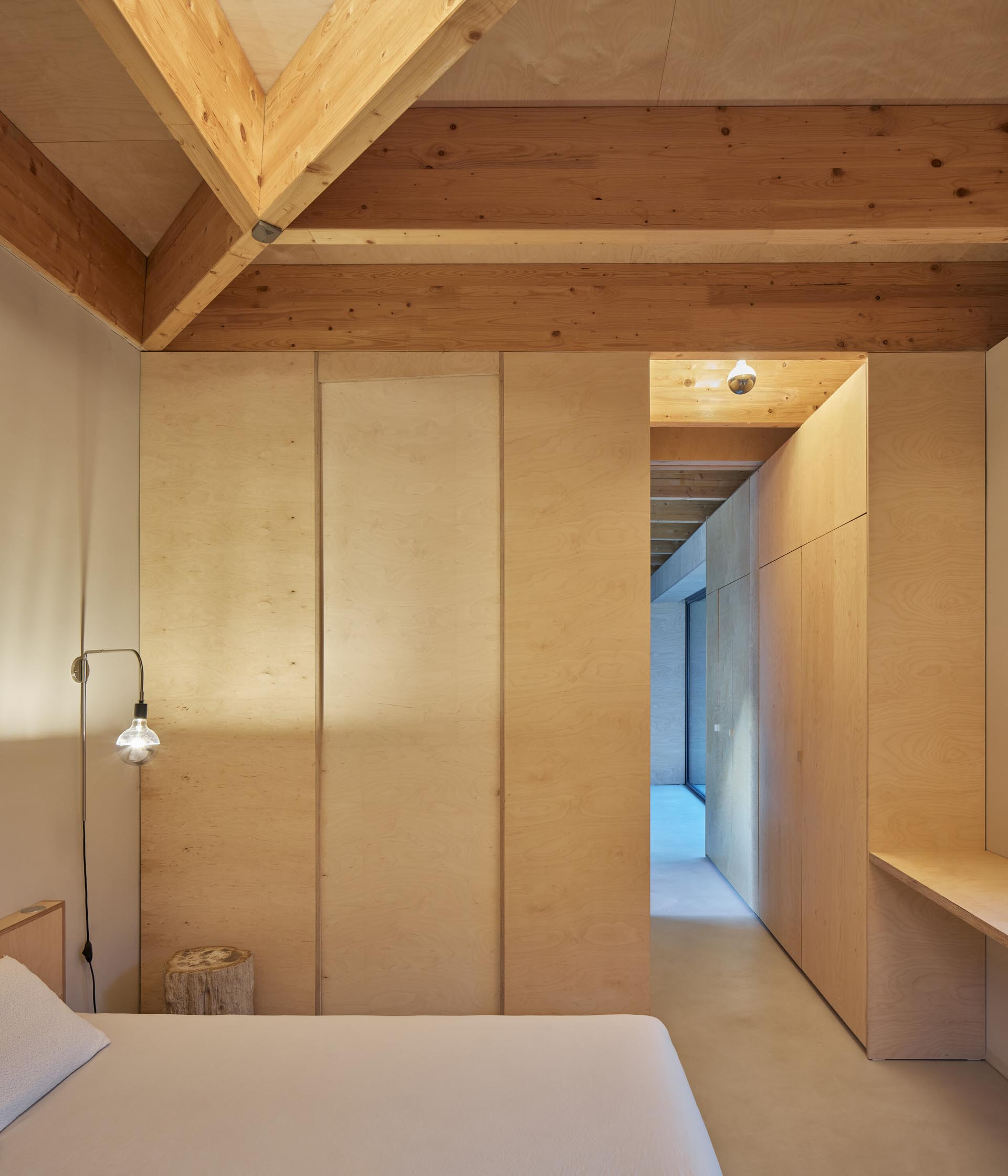 Plywood closets line the hallway that leads to a bedroom, which is minimally furnished.