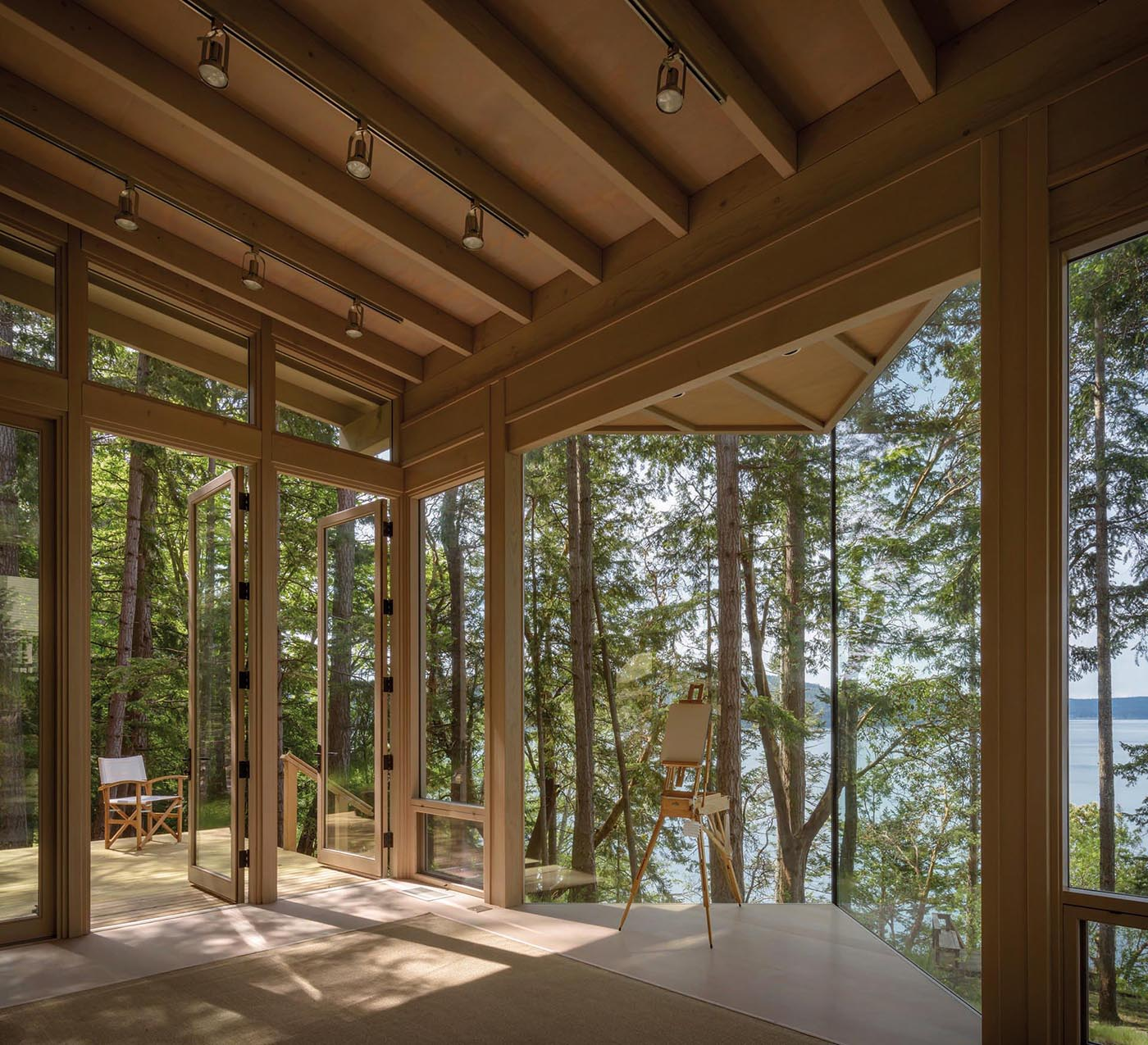 A small wood cabin that's designed as an artist cabin or guest house, and has glass walls.