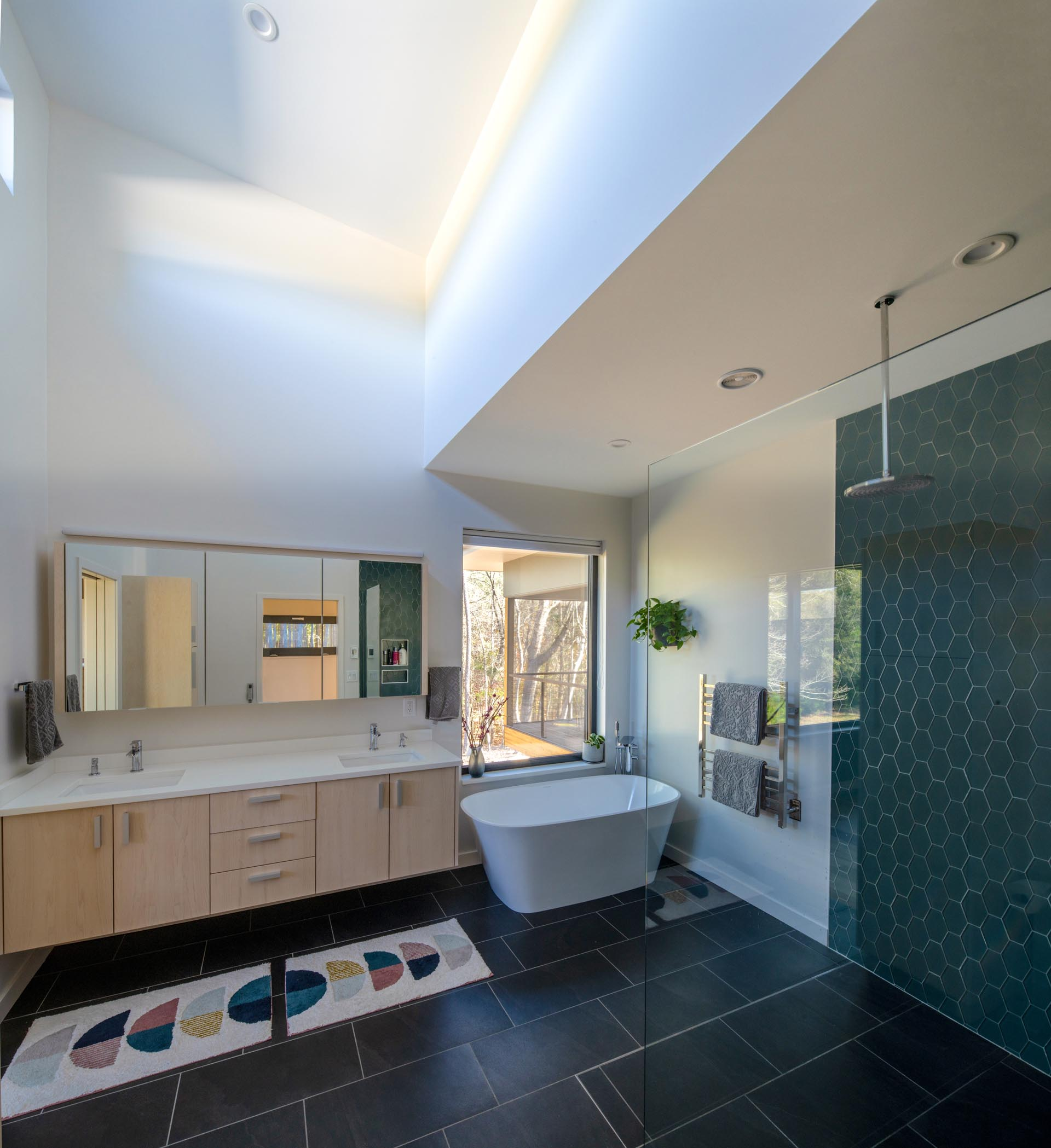 This spa-like master bathroom has high ceiling, black floor tiles, a dual sink vanity, a deep soaking tub, and a shower with a hexagonal tile accent wall.
