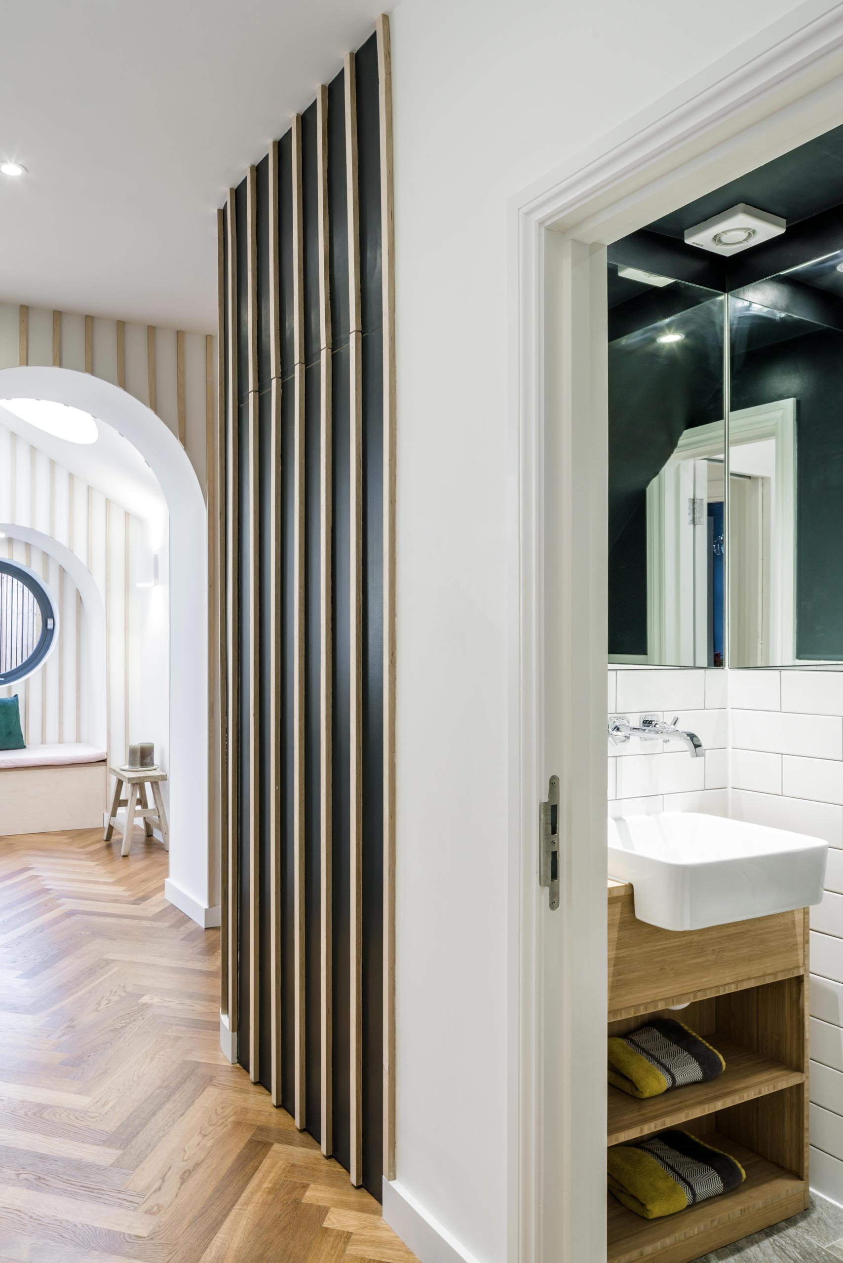 A small powder room that includes a dark ceiling, mirrors that the line the corner, a wood vanity, and white tiles.