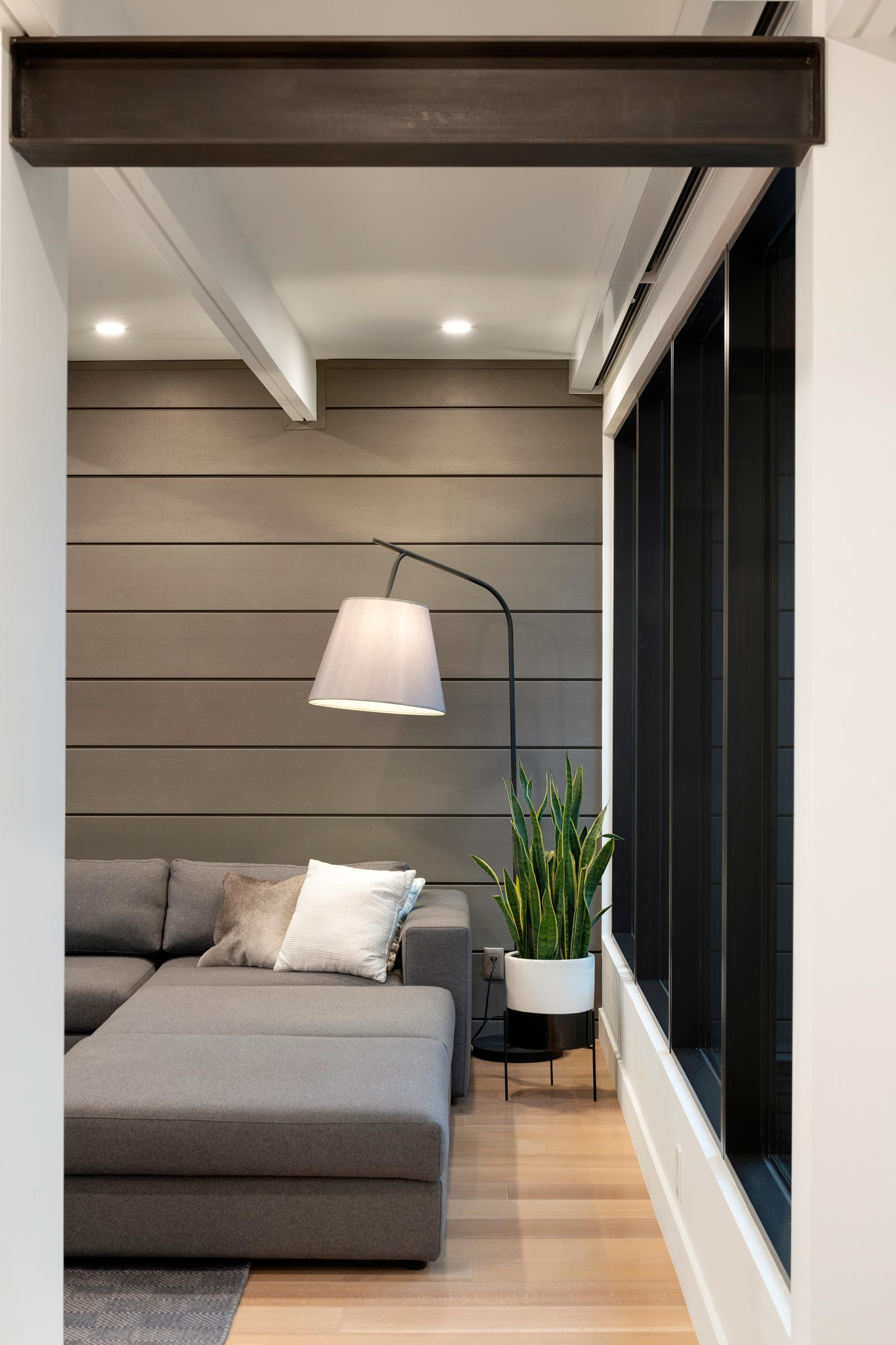 A modern living room with a gray paneled wall and matching sofa.