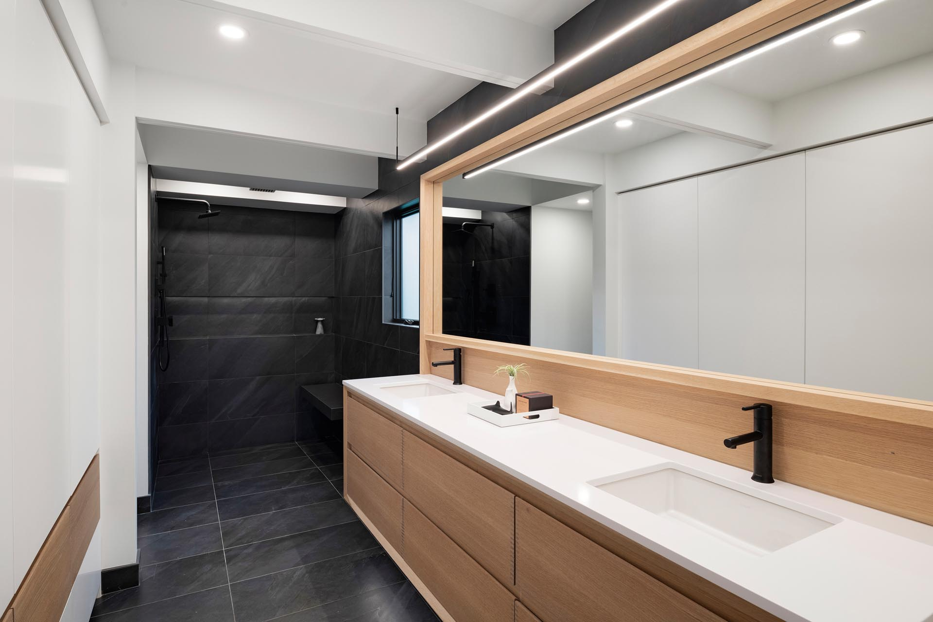 In this mdoern master bathroom, a long wood vanity is topped with a white counter and undermount sinks, while black tile has been used for flooring and the shower.