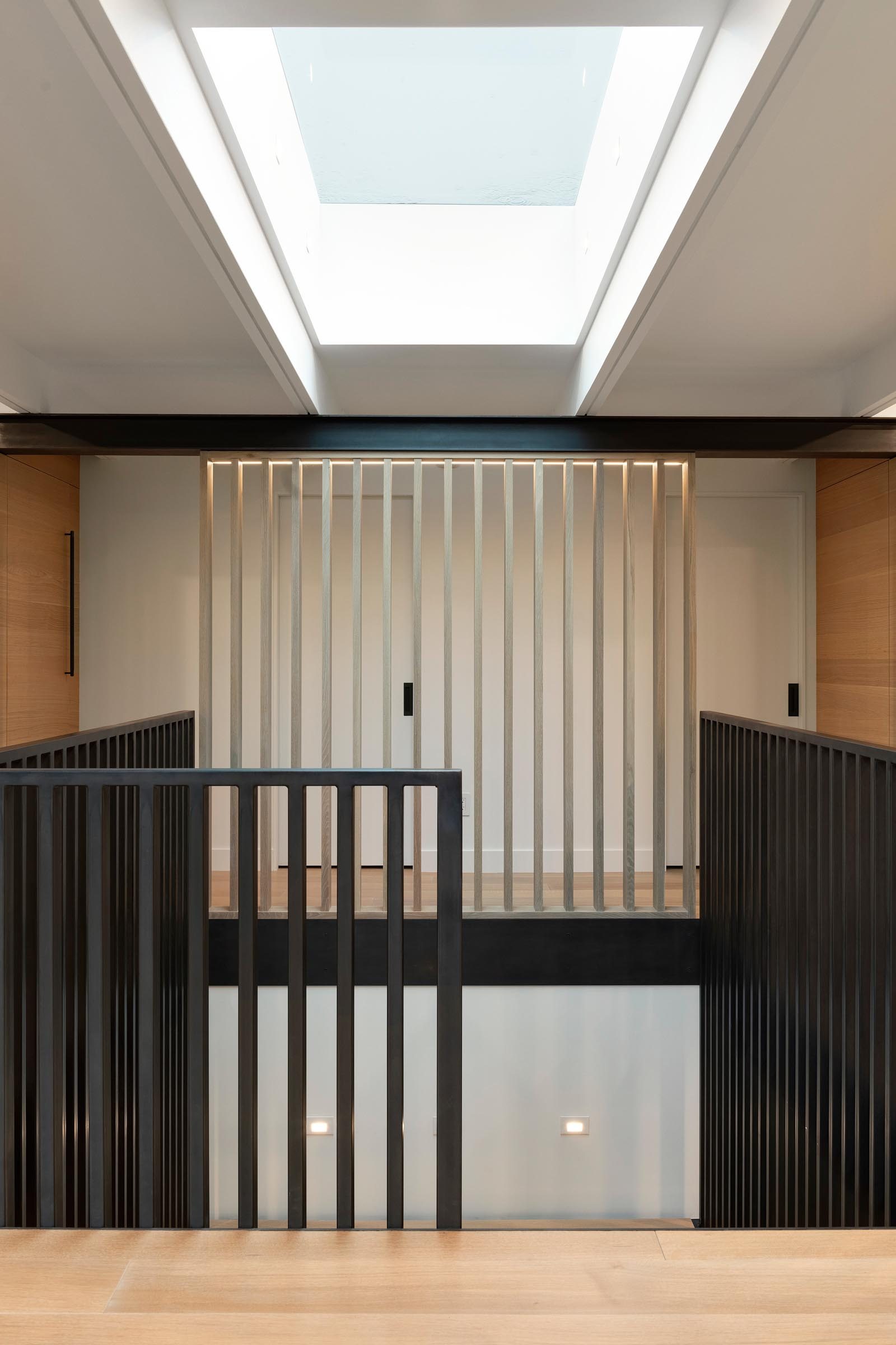 A skylight by the front door filters natural light through to the staircase that leads to the lower level of the home and features black handrails.