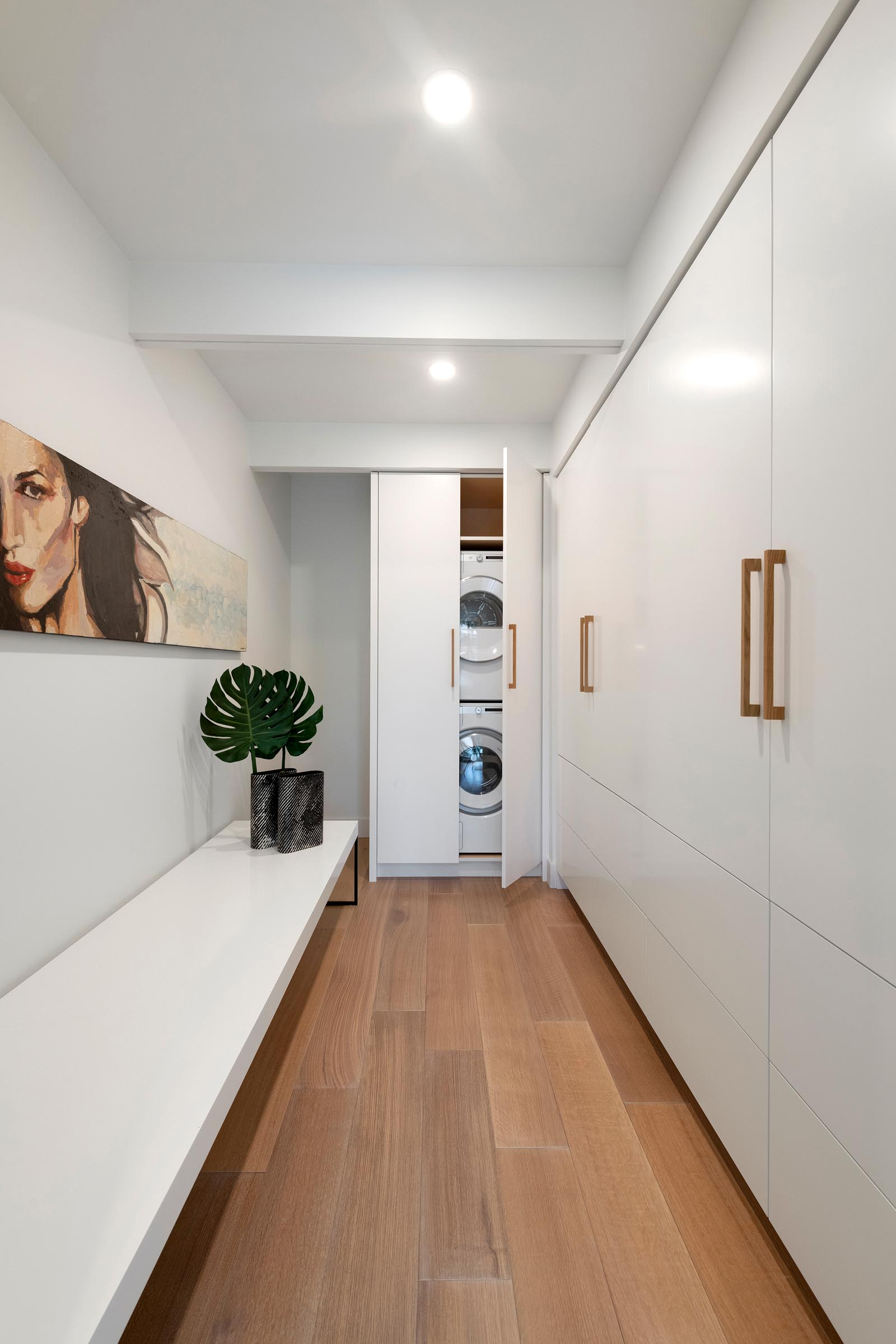 In this modern white laundry room, there's a long bench and wall of cabinetry with a washer and dryer hidden in the end cabinet.