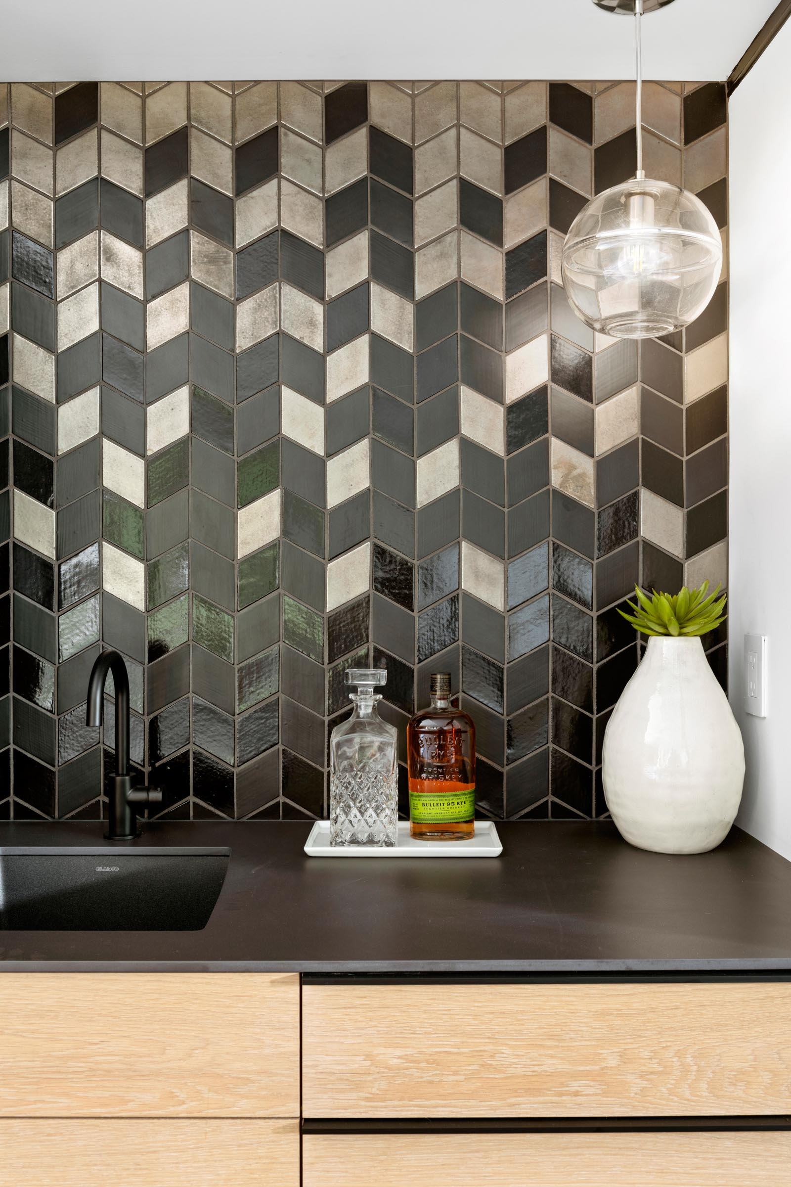 A modern bar area with a matte and glossy tiled wall that matches the black countertop.