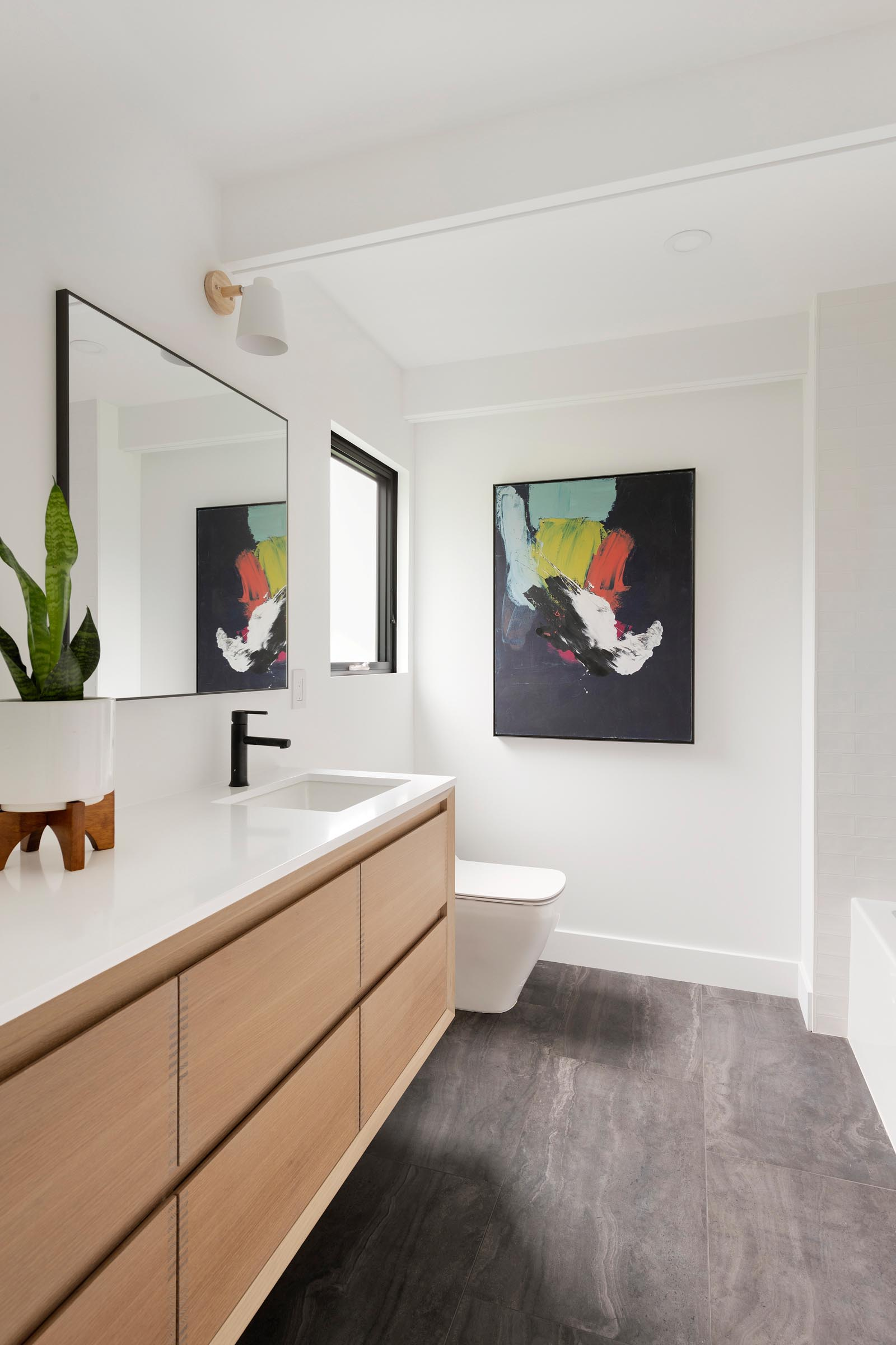 In this modern bathroom, white walls and a light wood vanity keep the space bright, and artwork adds a colorful element.
