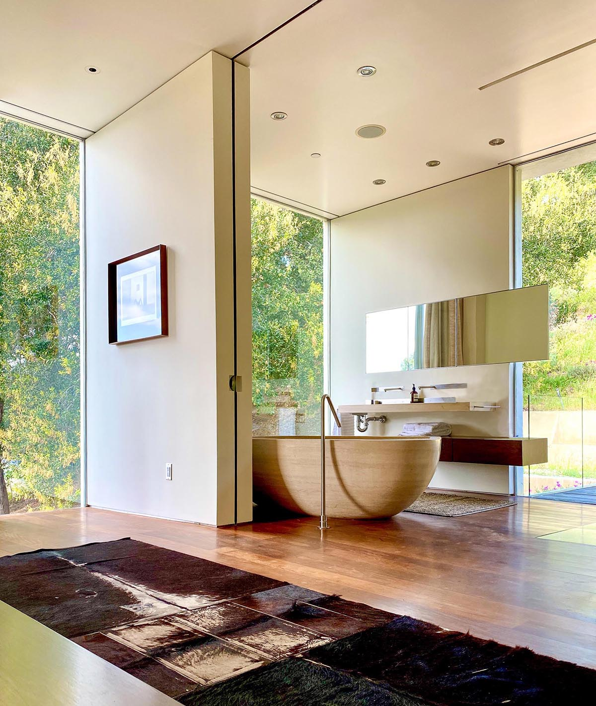 A modern master bathroom includes Portuguese limestone and a soaking tub that's been hand-carved from a single block.