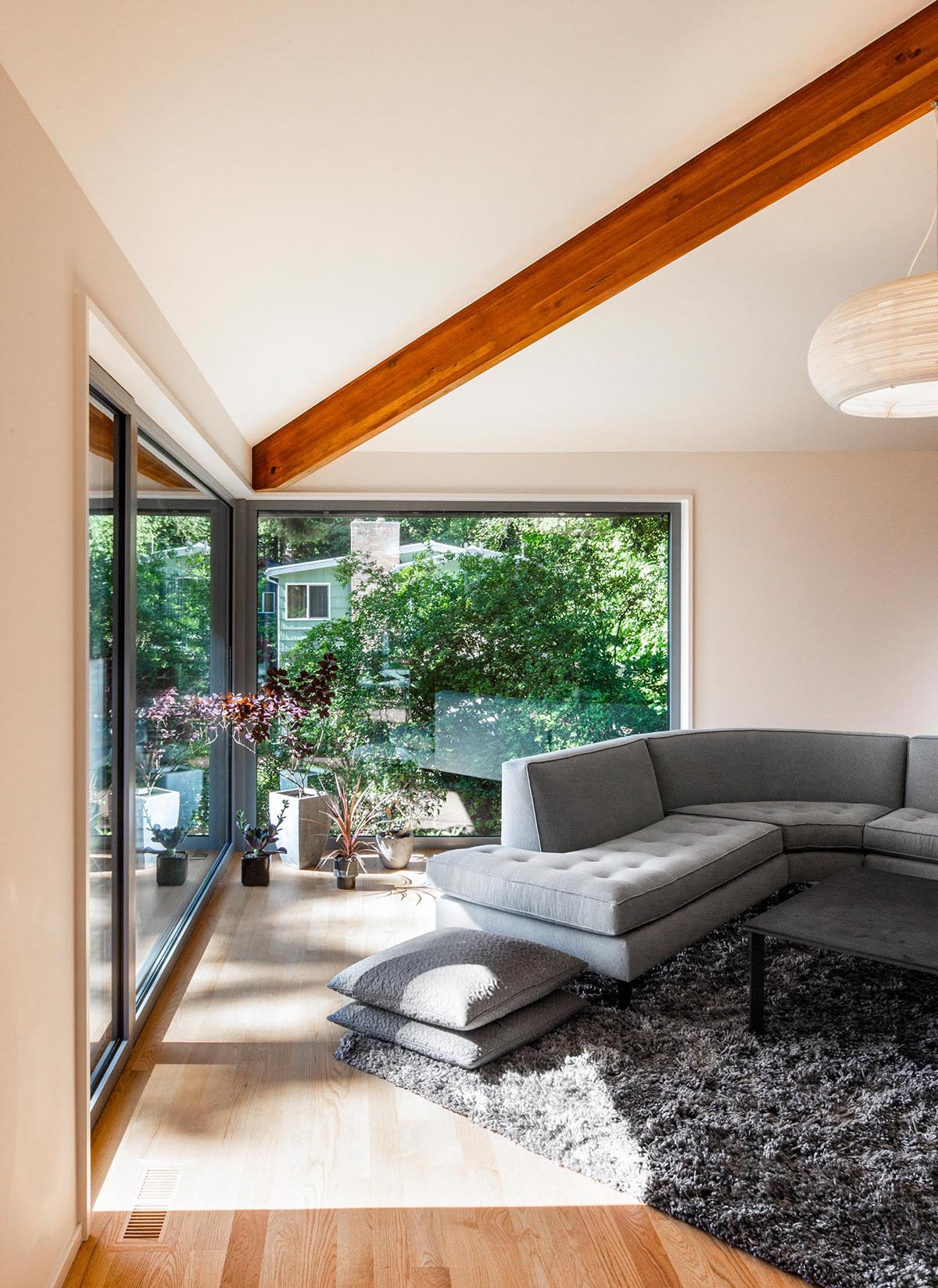A modern living room with large windows.