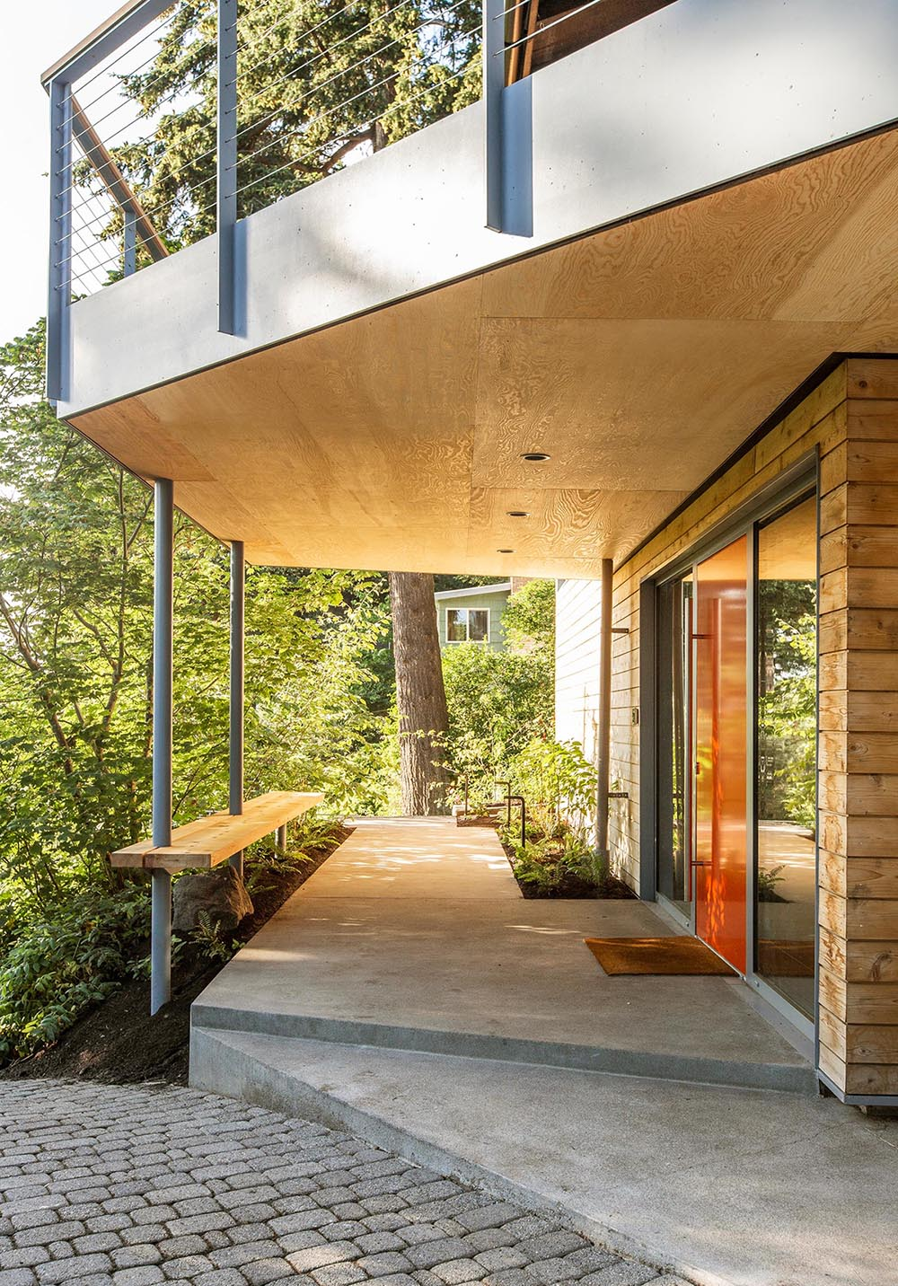A partially covered walkway with a cedar bench leads people to the front door.