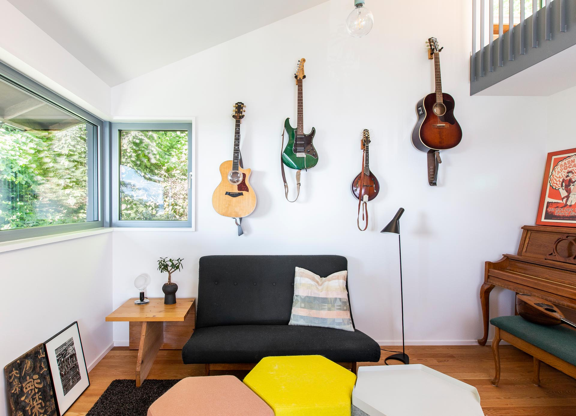 Tucked away in a small nook off a living room is a music corner, with hanging guitars, a piano, and a small sofa.