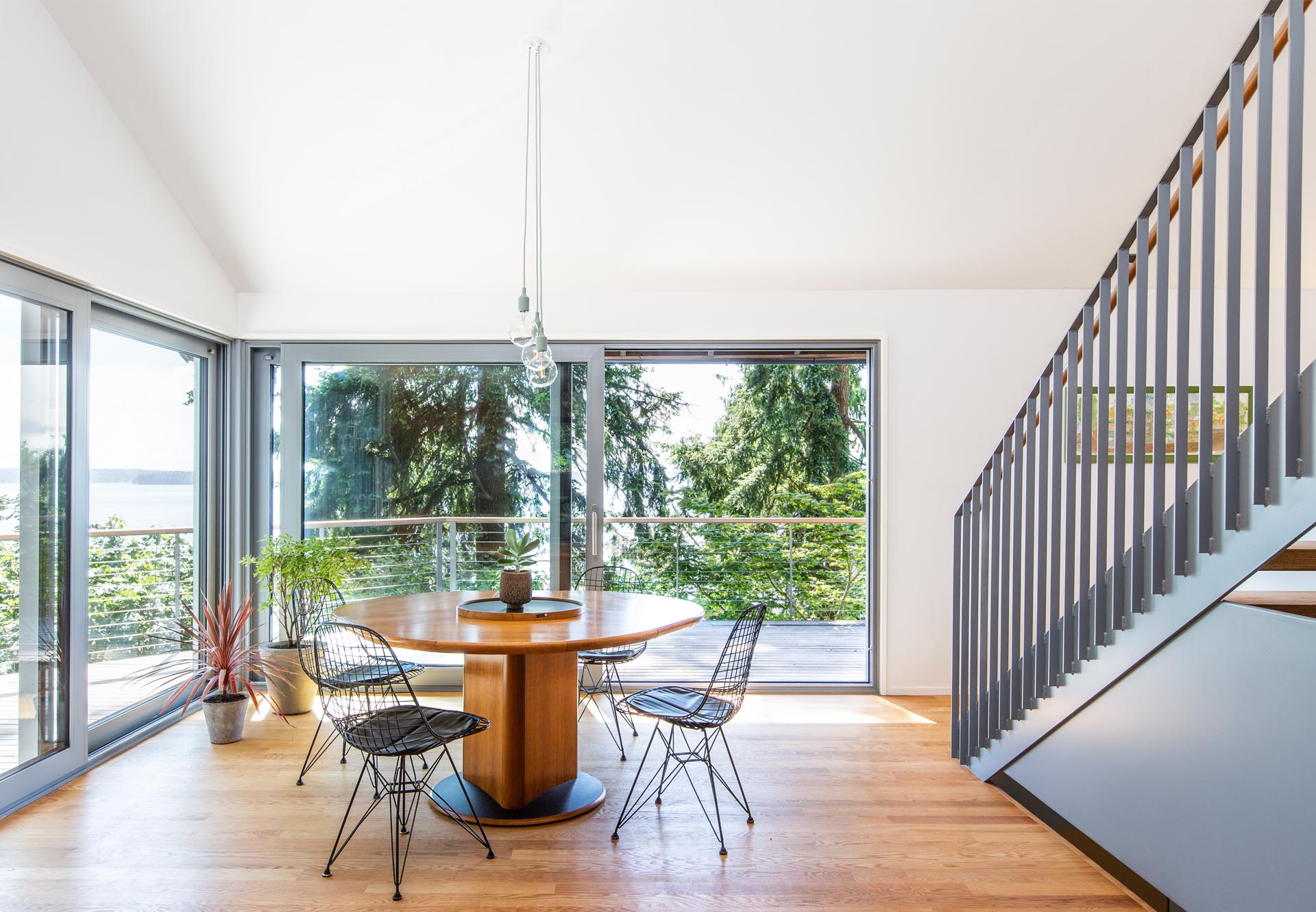 A dining room with a round wood table and sliding doors that open to the balcony.