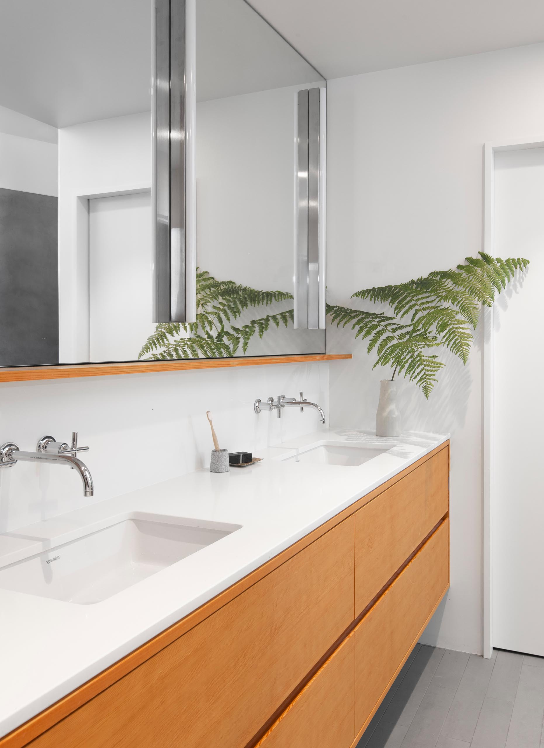 In this modern master bathroom, a Caesarstone 'Pure White' countertop sits atop a fir vanity with recessed pulls.