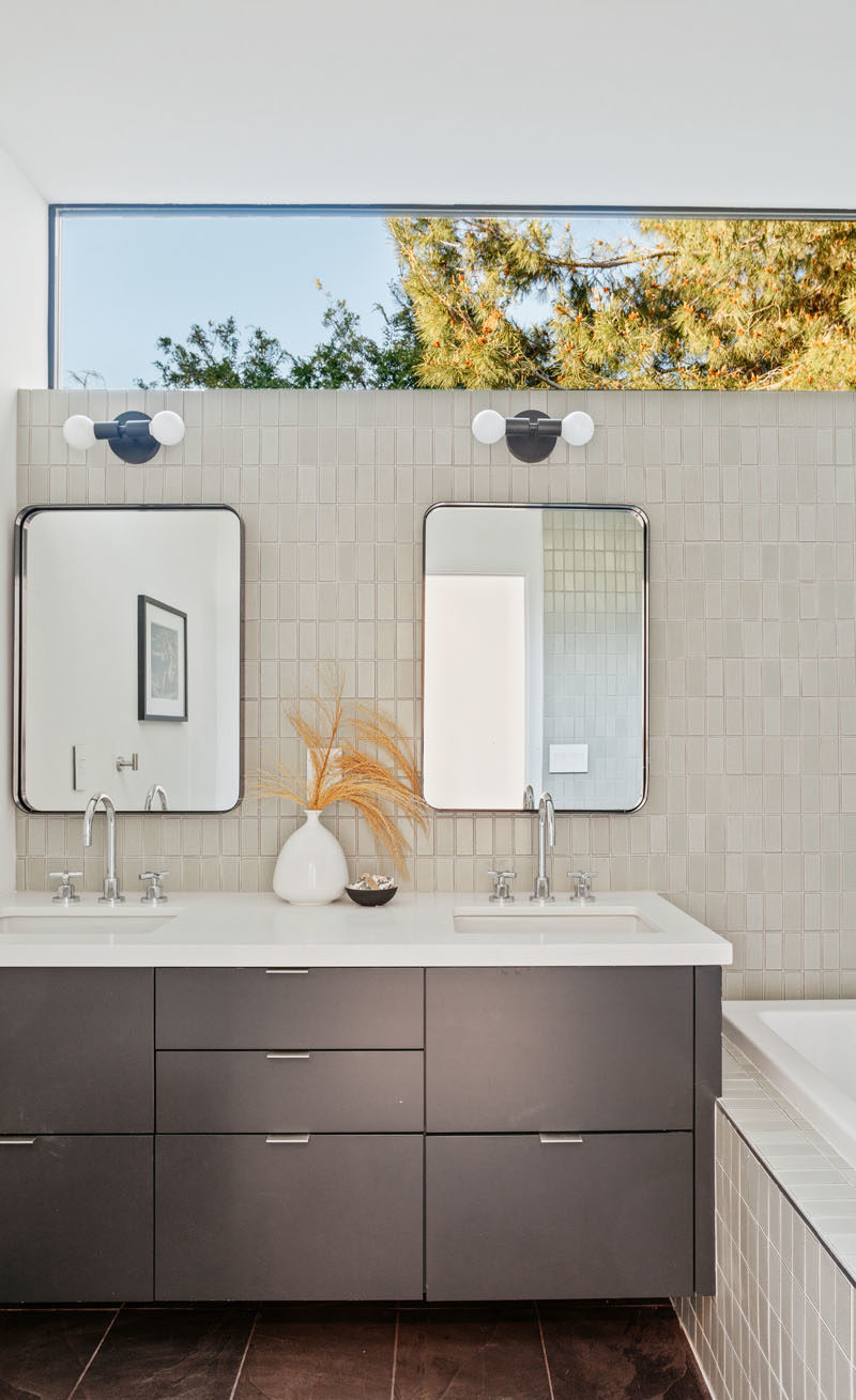 Bathroom Ideas - This modern bathroom features clerestory windows that provide a glimpse of the trees, while a bathtub has been built-in beside the vanity. #BathroomIdeas #ModernBathroom #BathroomDesign