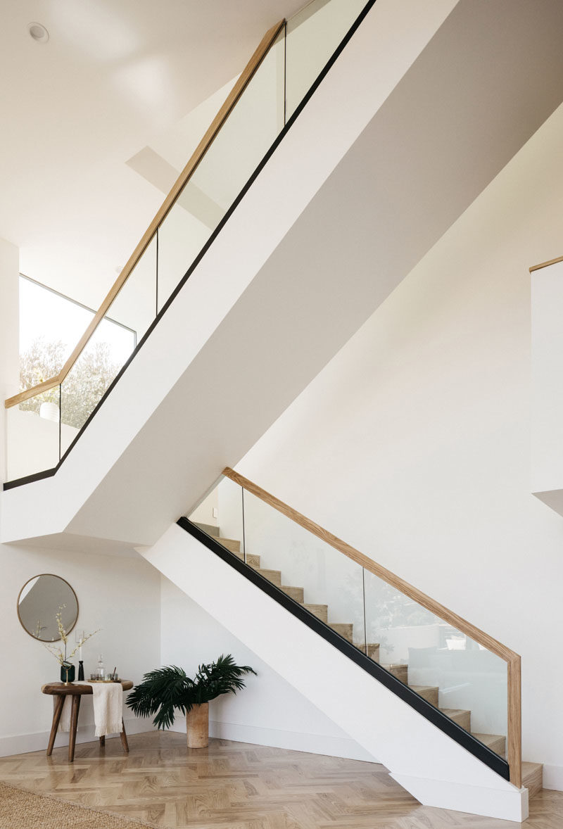 Stair Ideas - This modern house has a large staircase with glass and wood handrails. #Stairs #StairIdeas #ModernStairs #LivingRoomIdeas