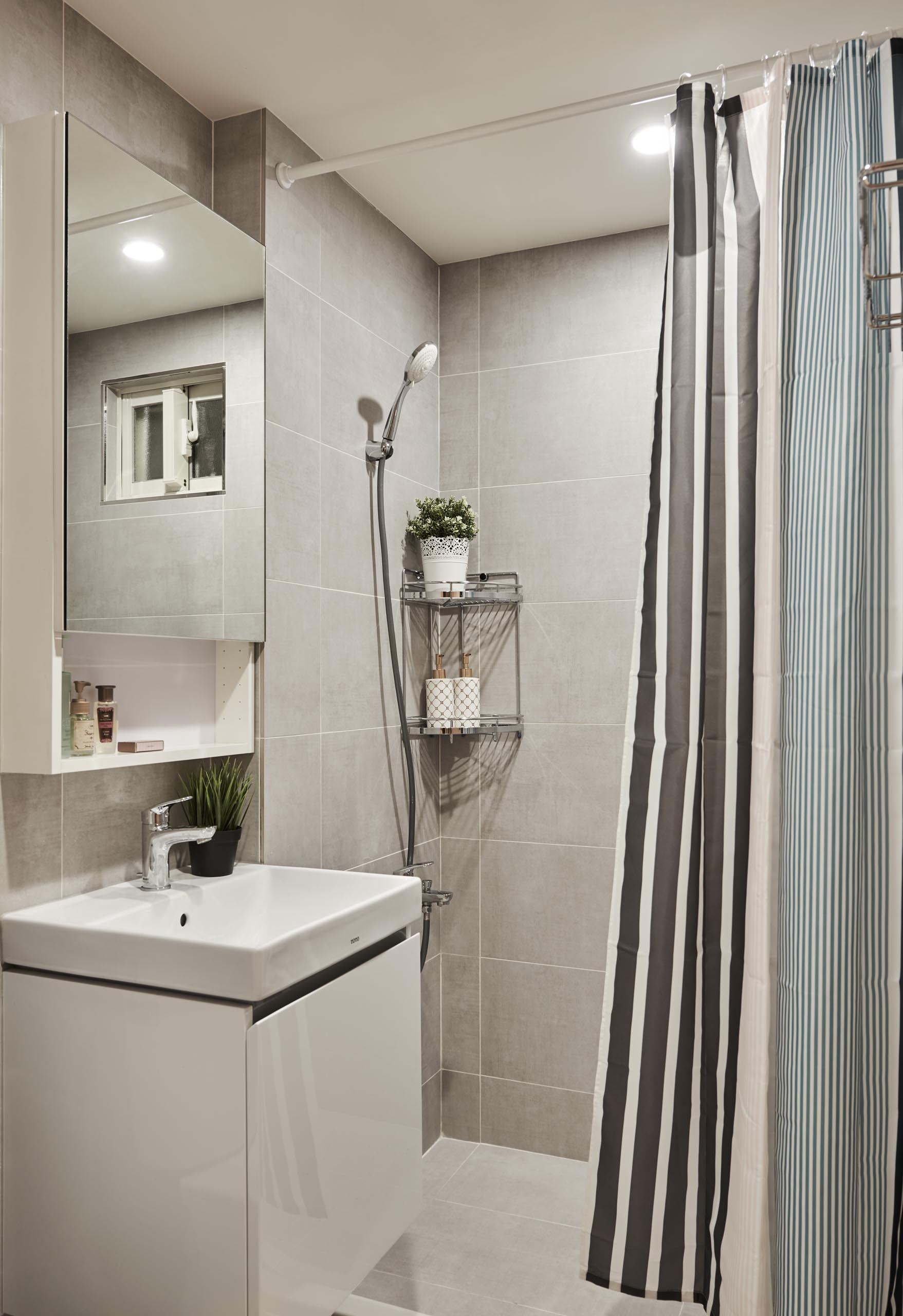 In this small bathroom, there's large format tiles that cover the walls and floors.