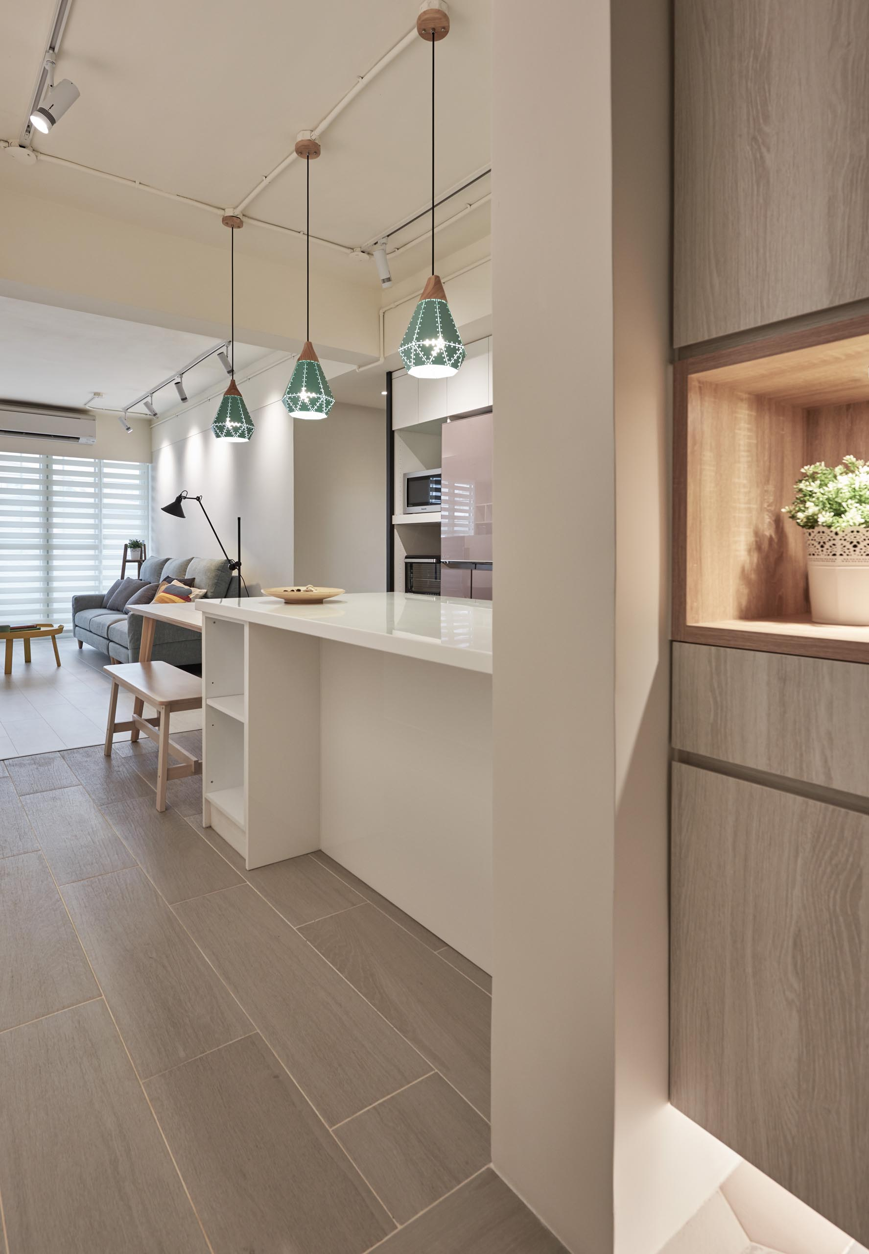 In this apartment kitchen, three pendant lights with a geometric design hang above a peninsula that connects with a dining table, while minimalist hardware-free white kitchen cabinets help to the keep the interior bright.