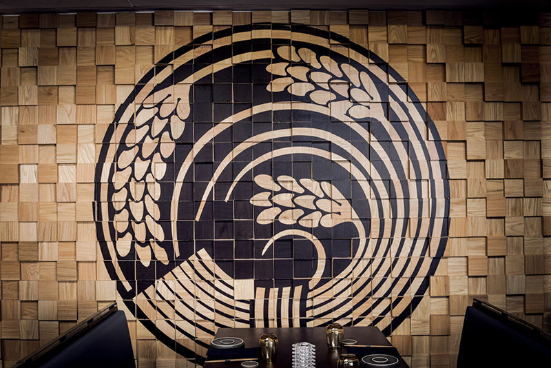 Wall Decor Idea - Murals On Painted Wood Blocks. The wood block wall in this restaurant is filled with Japanese-inspired murals, that have been painted in black.