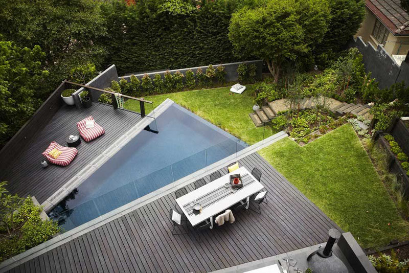 16 Inspirational Backyard Landscape Designs As Seen From Above // This tiered backyard has different levels, a pool level and a dining area separated by a glass wall, this would be the perfect place for a family gathering. #Backyard #YardIdeas #LandscapingIdeas #YardLayout #YardDesign
