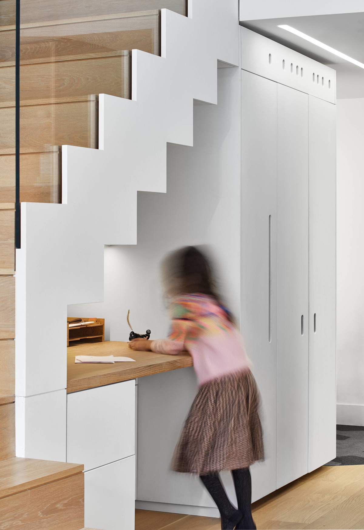 A built-in desk has been included underneath the stairs in a modern loft apartment.
