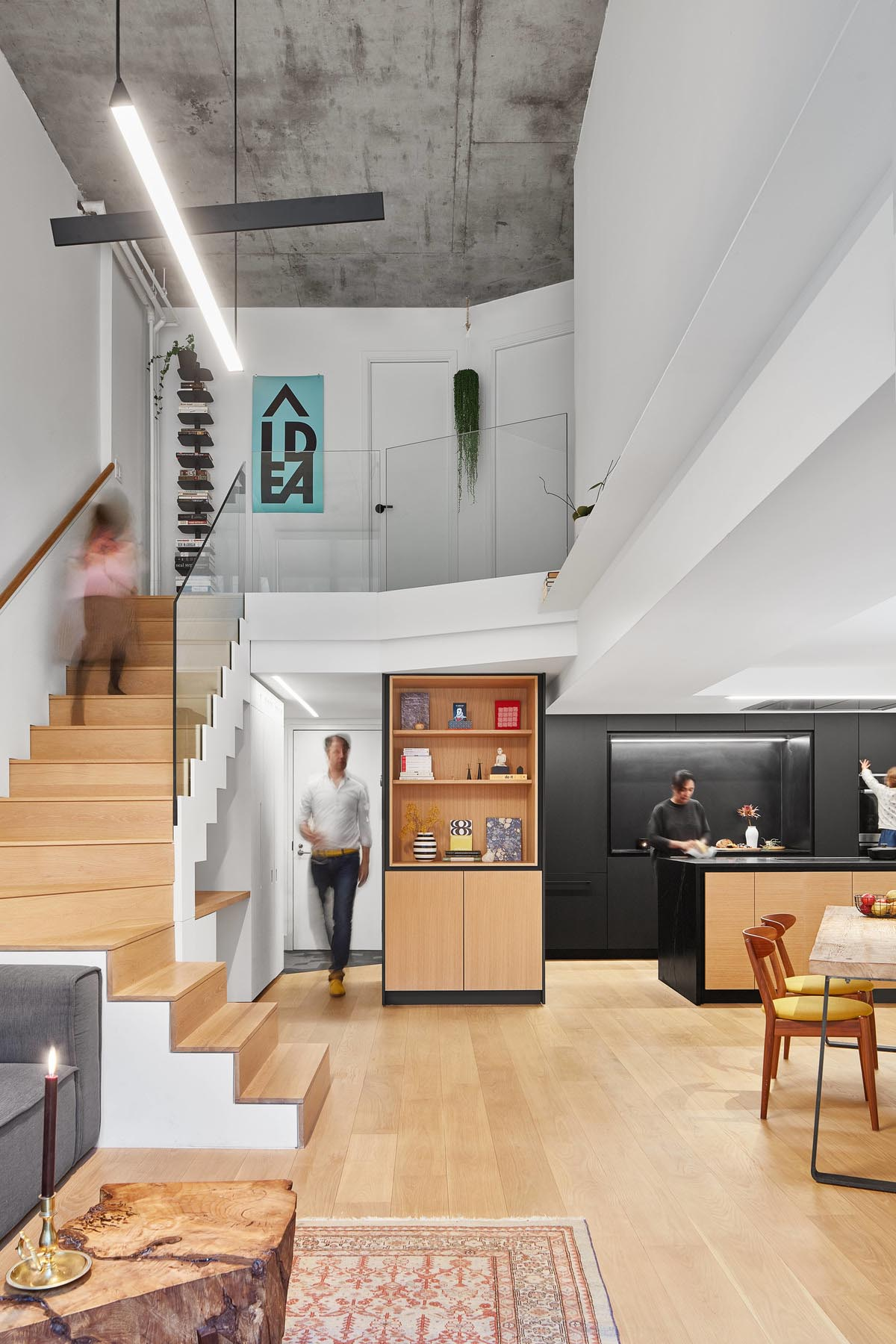 A modern loft apartment with a matte black kitchen and a built-in desk under the stairs.