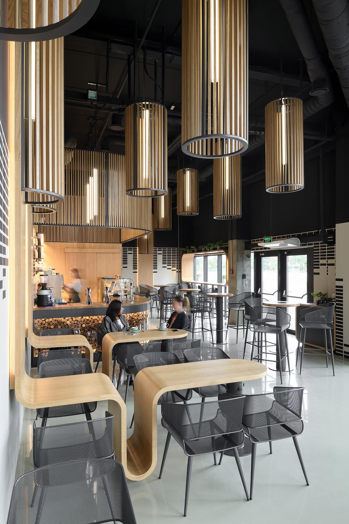 A modern coffee shop with custom designed oak tables that continue onto the wall.