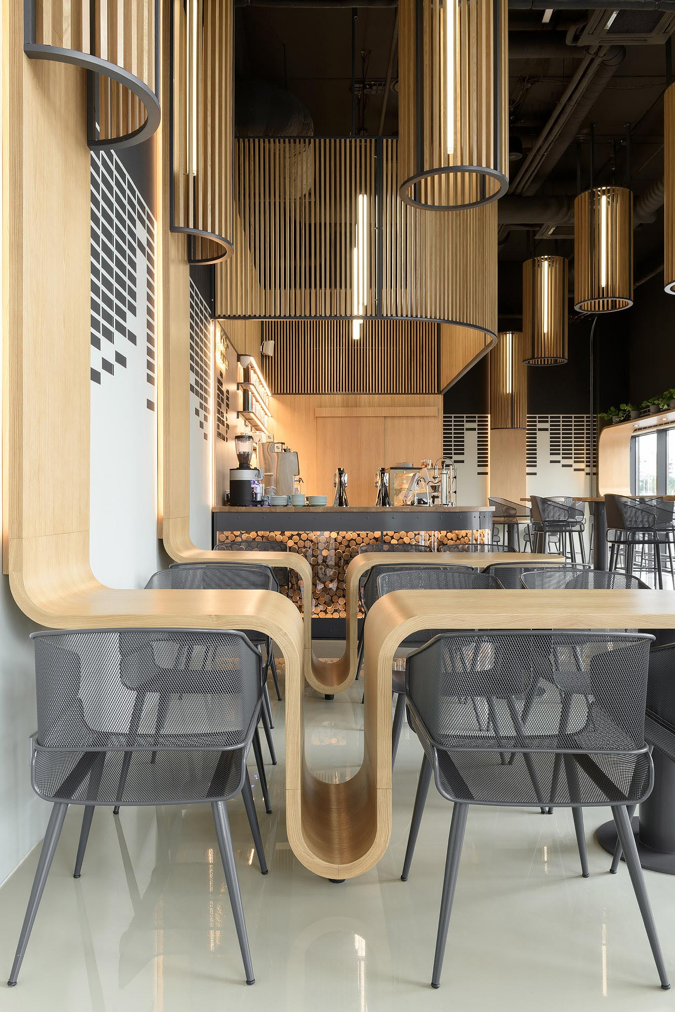A modern coffee shop with custom designed oak tables that continue onto the wall, and have space for bags to be placed.