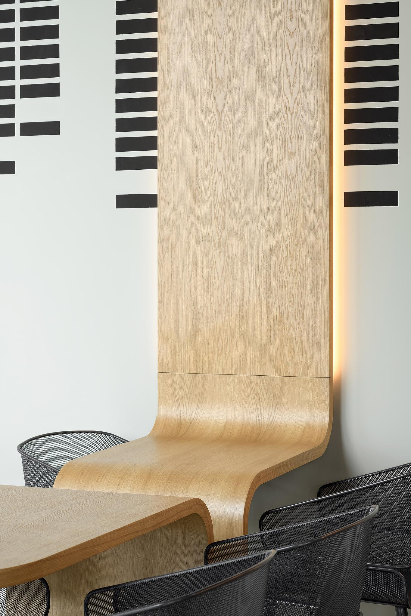 A modern coffee shop with custom designed oak tables that continue onto the wall and have hidden LED lighting.